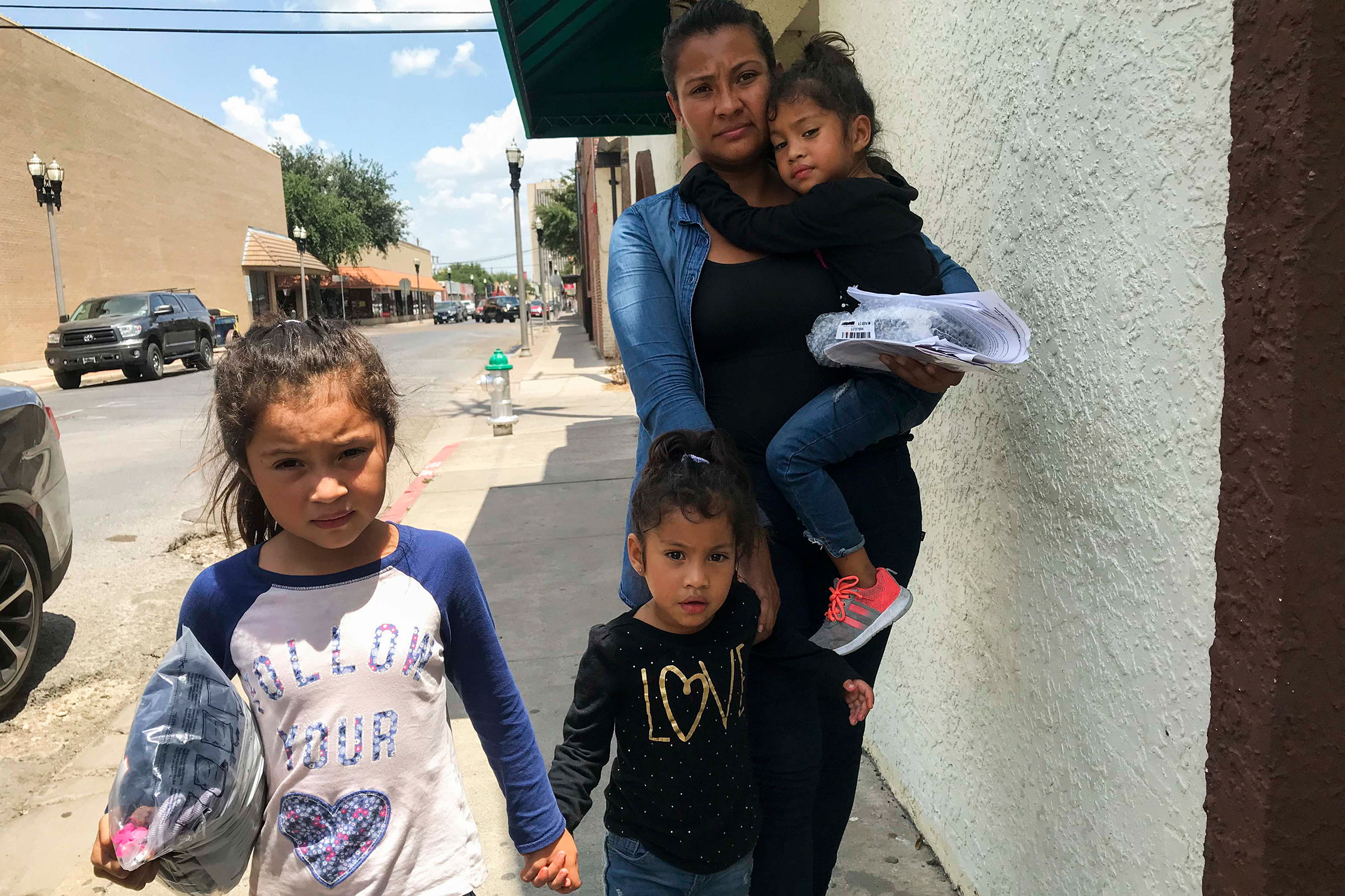 Silvia Guidel and her daughters Seily, 7, and twins Nahsliy Nicole and Nahsliy Dariana, 4, from Guatemala, make their way from the McAllen bus station to the Catholic Charities Humanitarian Respite Center on July 31, 2018.
