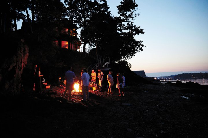 People gathered around a fire at The Lost Kitchen is Freedom