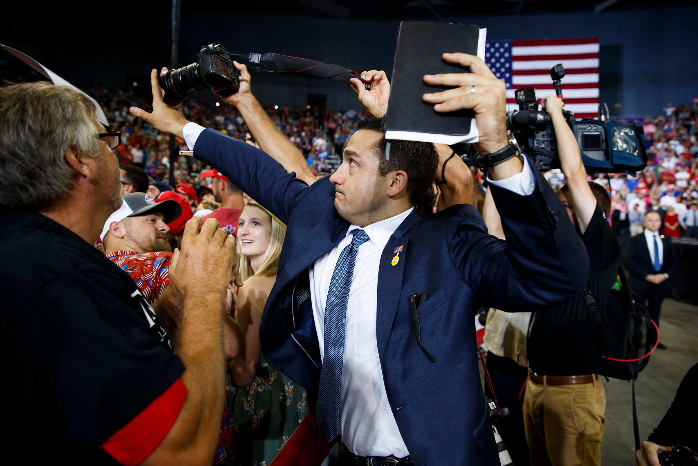 A Trump campaign volunteer blocks a camera as a photojournalist attempts to take a photo of a protester during a campaign rally at the Ford Center, in Evansville, Ind, August 30, 2018.