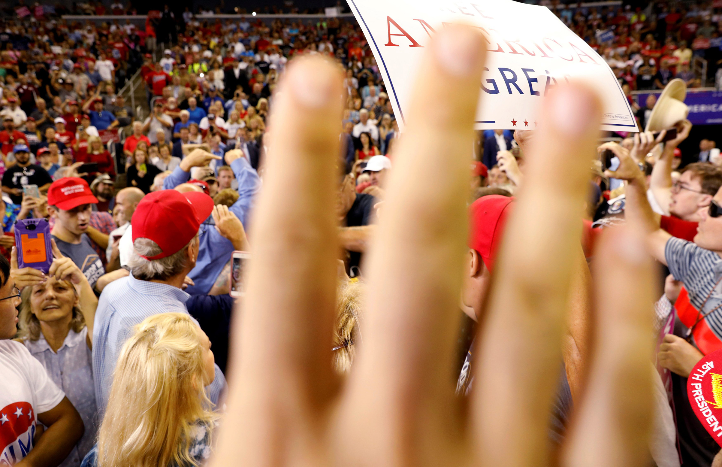 A volunteer for Trump attempts to block the view of protesters a  Make America Great Again  rally in Evansville, Indiana, August 30, 2018.