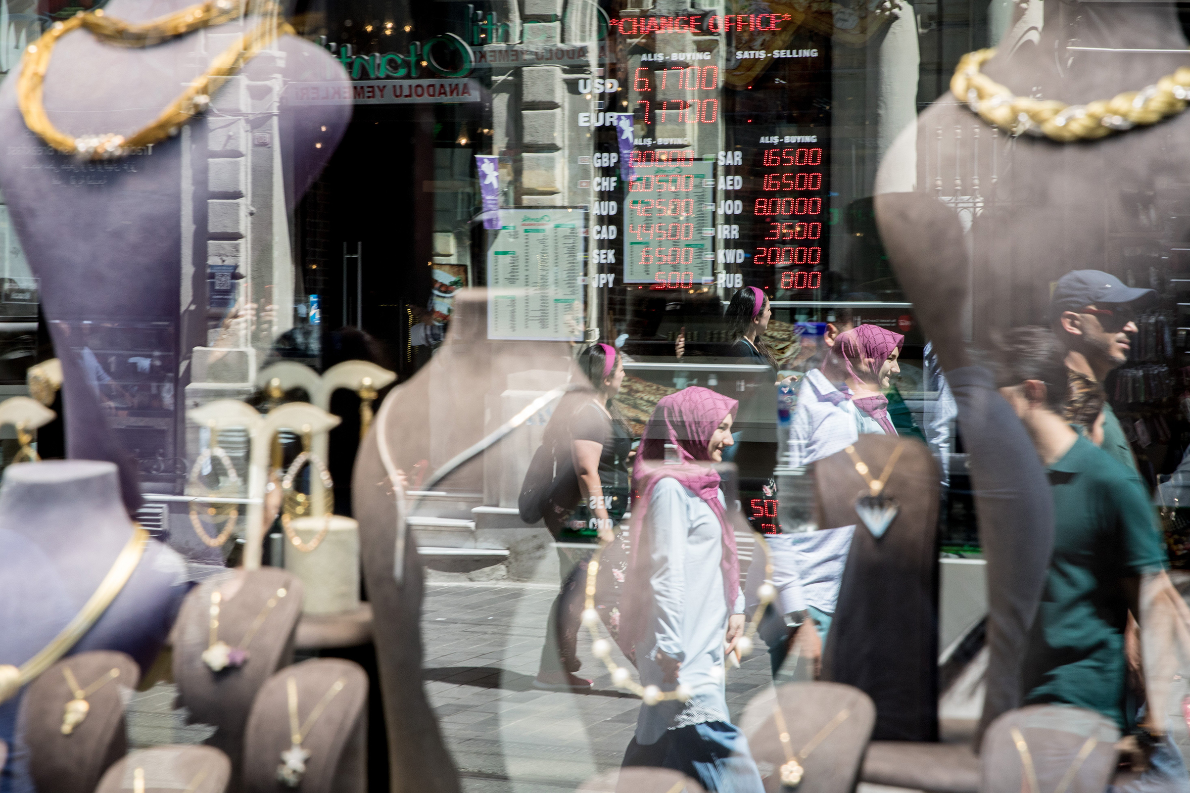 People are reflected on the street as they pass a  currency exchange office on August 13, 2018 in Istanbul, Turkey. The lira hit another record low overnight forcing Turkey's Central Bank to act to curb the lira's collapse, however the action was not enough to subdue investors fears over the countries financial crisis.