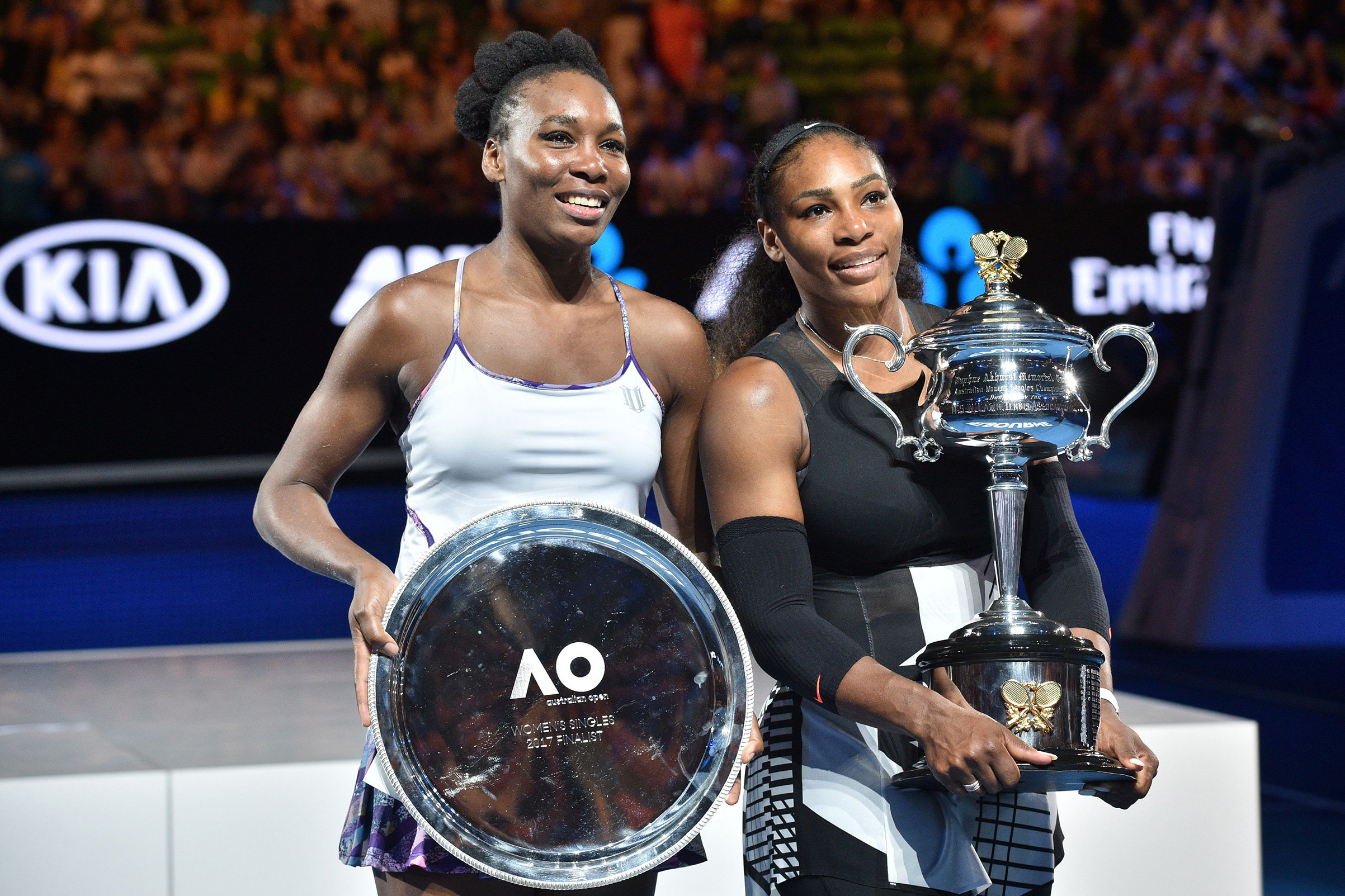 Serena Williams of the US (R) celebrates with the championship trophy during the awards ceremony after her victory against Venus Williams of the US in the women's singles final on day 13 of the Australian Open tennis tournament in Melbourne on January 28, 2017.