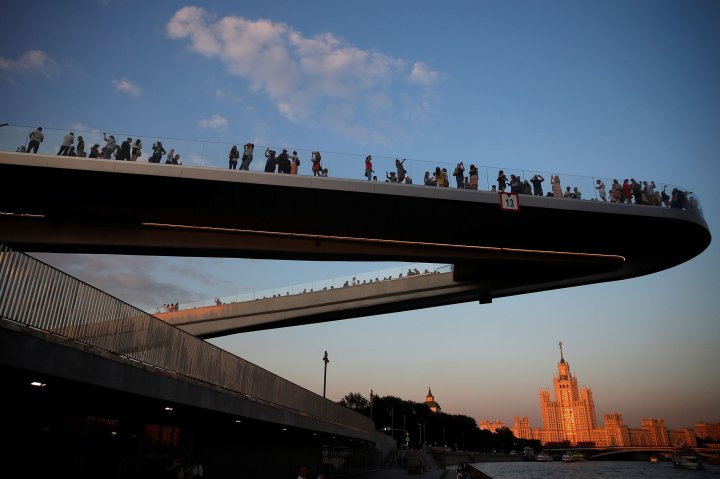 People walk on a pedestrian bridge over the Moskva river at the Zaryadye Park in Moscow
