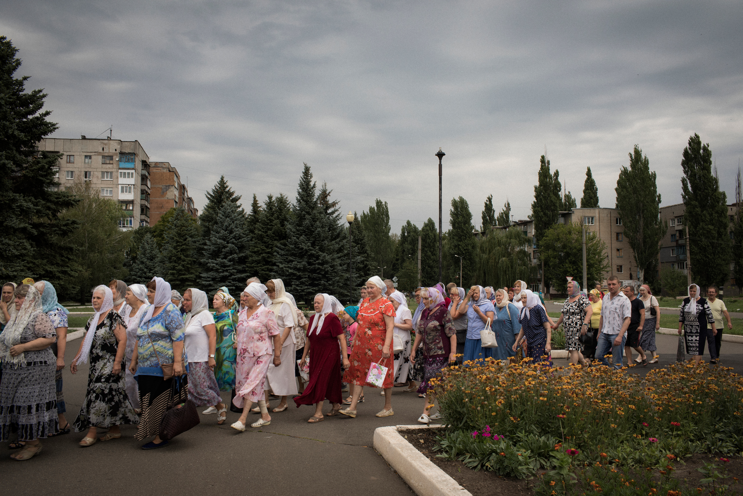 Parishioners participate in a procession in front of the Church of St. Mary Magdalene in Avdeevka. The church stands next to a minefield.
