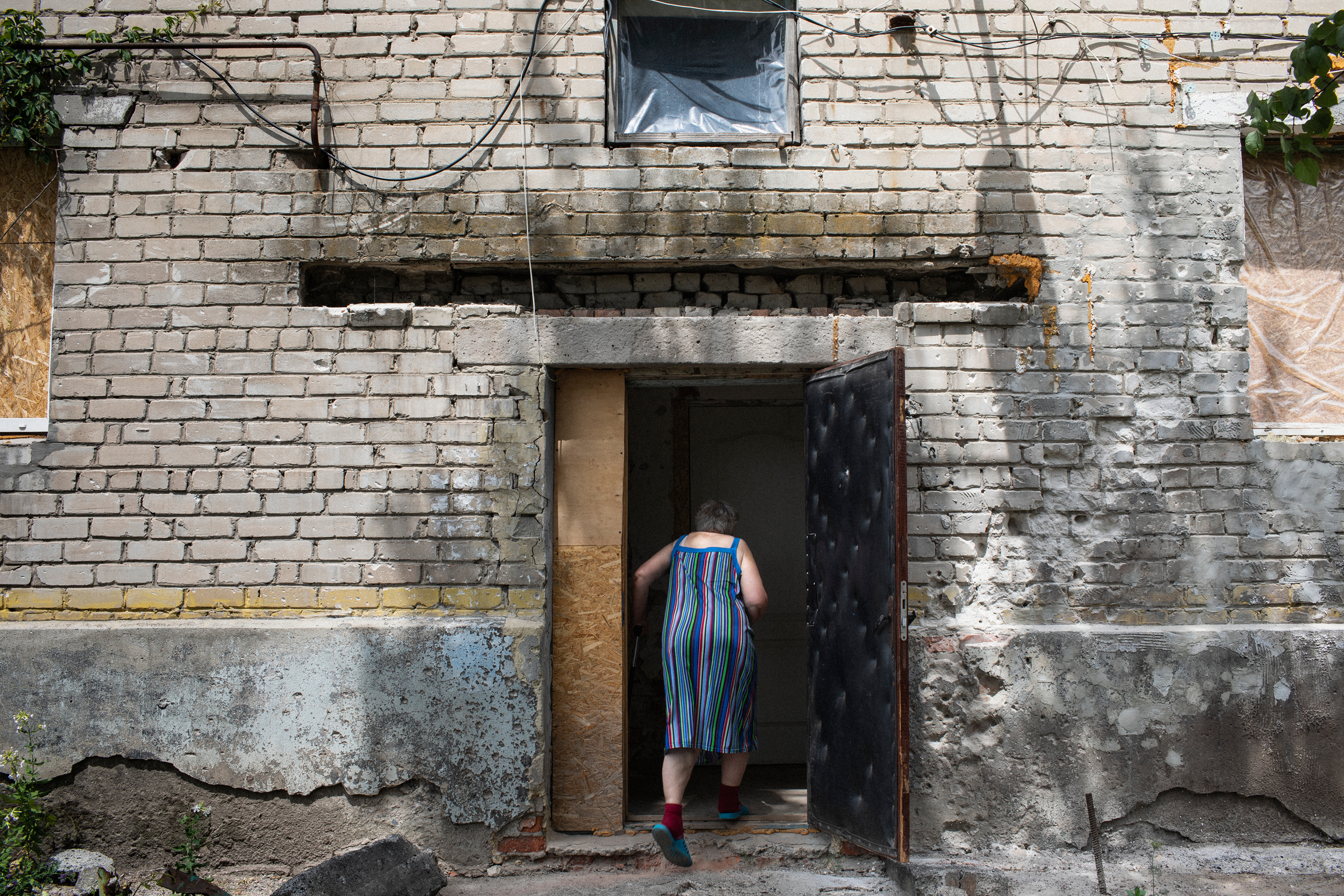 A woman walks into a home that has sustained shell damage in the village of Novoluganskoe. Eastern Ukraine is full of pensioners who have stayed behind, often due to a lack of money or physical strength.