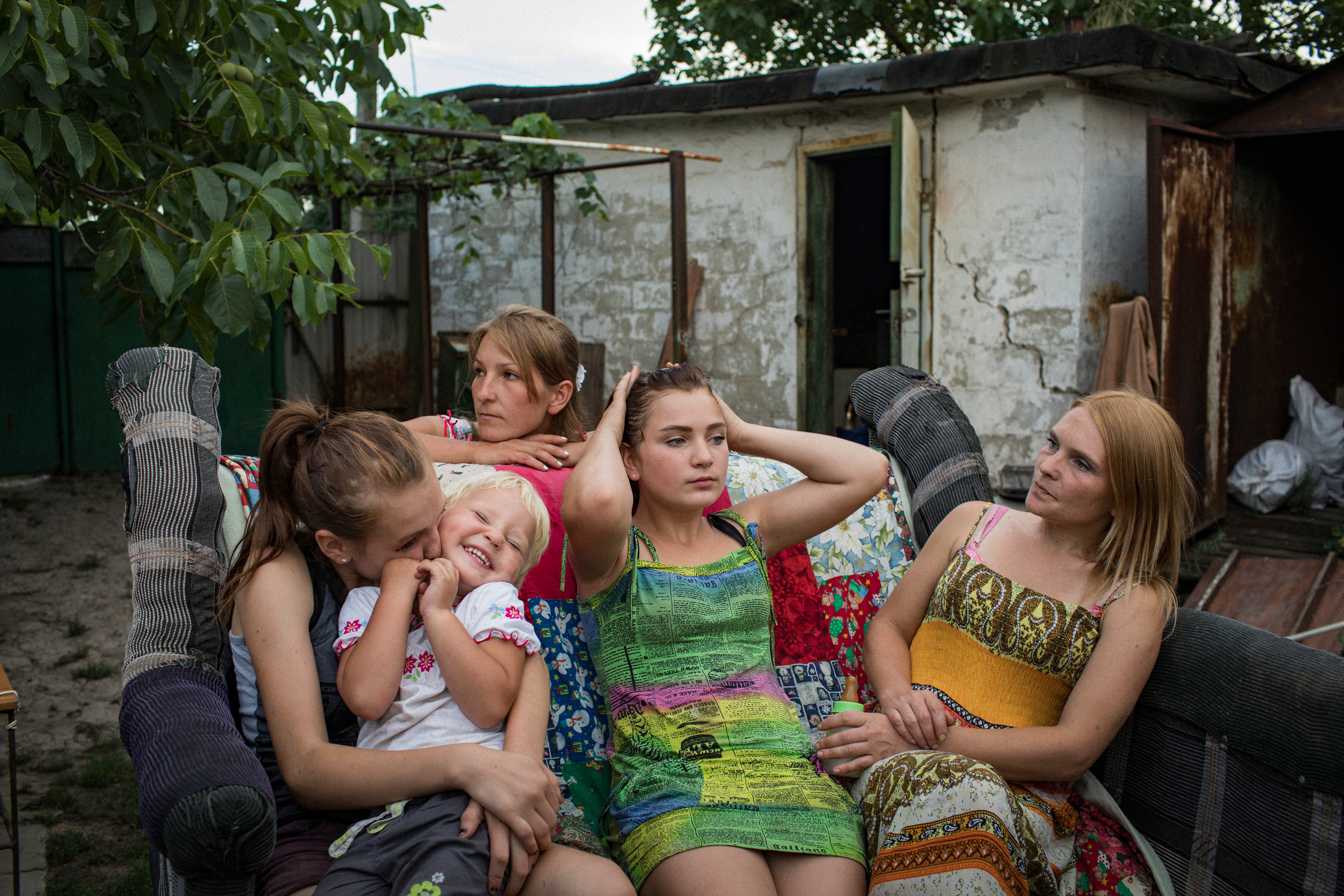Aleksandra Mountyan, Miroslava Grinik, Olga Grinik, Victoria Mountyan and Valentina Mountyan—all members of an extended family—hang out in the backyard of Olga's house, located 50 meters from a Ukrainian military position in old Avdeevka. People may appear relaxed to the sounds of shelling and gunfire, but it's an illusion: they listen to determine the degree of danger. Everyone knows the safest place in their home.