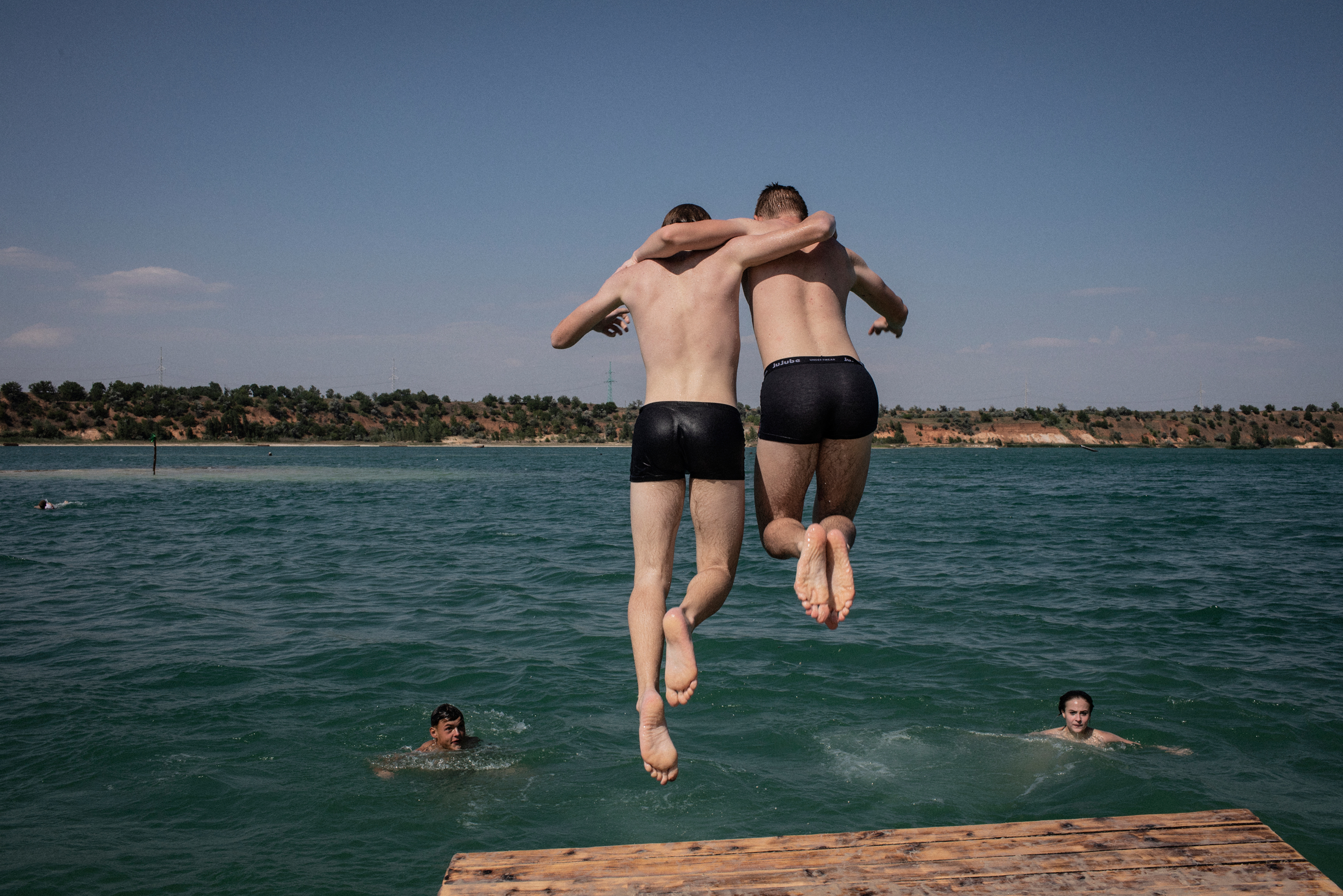 Two boys jump into the water at a sand quarry beach in Avdeevka. The quarry has suspended its work due to its close proximity to the frontline and shelling damage to the equipment, but is still used as a recreational area.