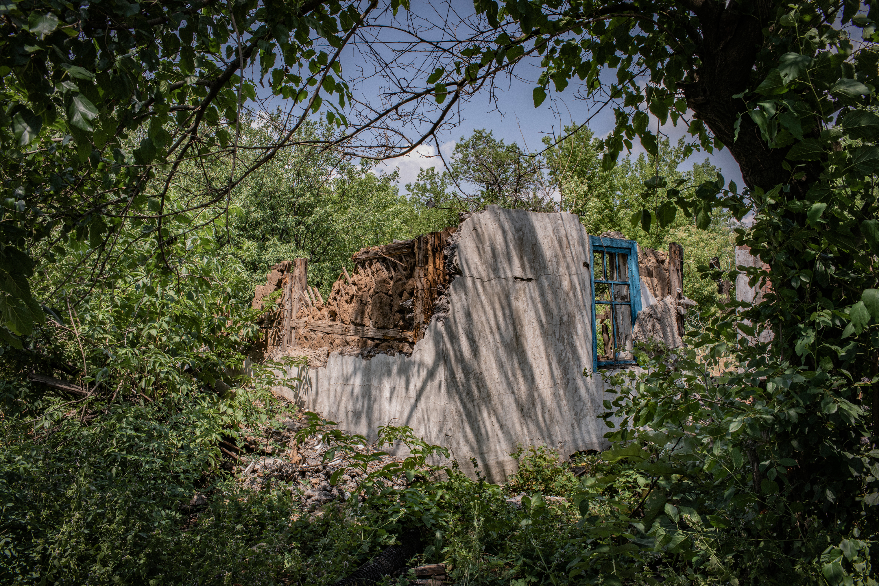 A house that was destroyed by shelling in Yuzhnaya, a frontline area near Toretsk. It's easy for outsiders to see only broken walls, collapsed ceilings and a mess of the mutilated furniture and wallpaper. Yet locals still see their homes, and carry stories about the lives they lived in them.