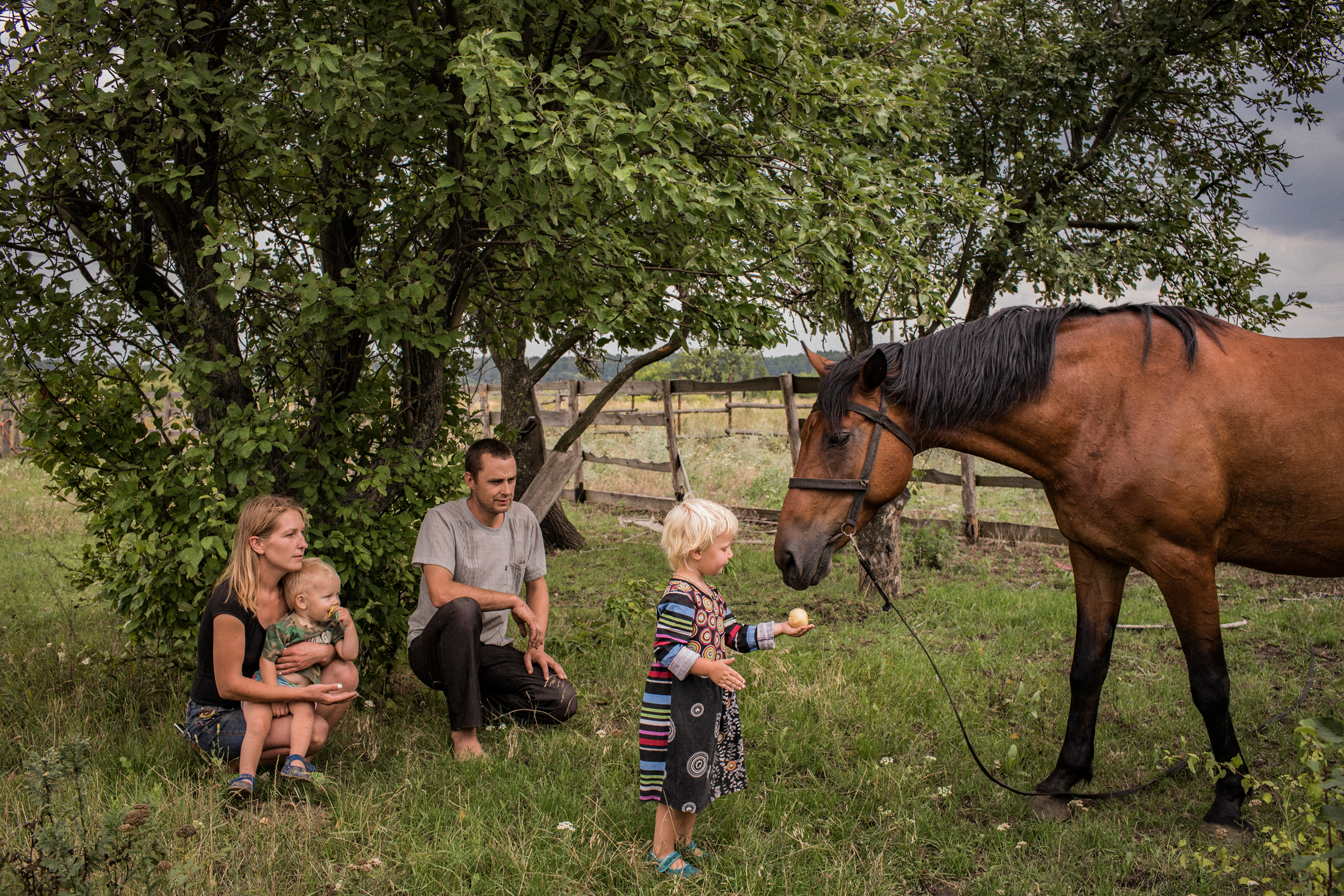 Olga and Nikolay Grinik in old Avdeevka. Both of their children were born during the war, and they joke about it:  In 2014, we were sitting without electricity for three months because of fighting. Nine months later, our daughter Miroslava (right) was born. In 2016, we had no light for a month, and nine months later we got our son Kirill (left). How else you gonna entertain yourself in the darkness? Now,  says Nikolay,  we pray there is no electricity outage again.""