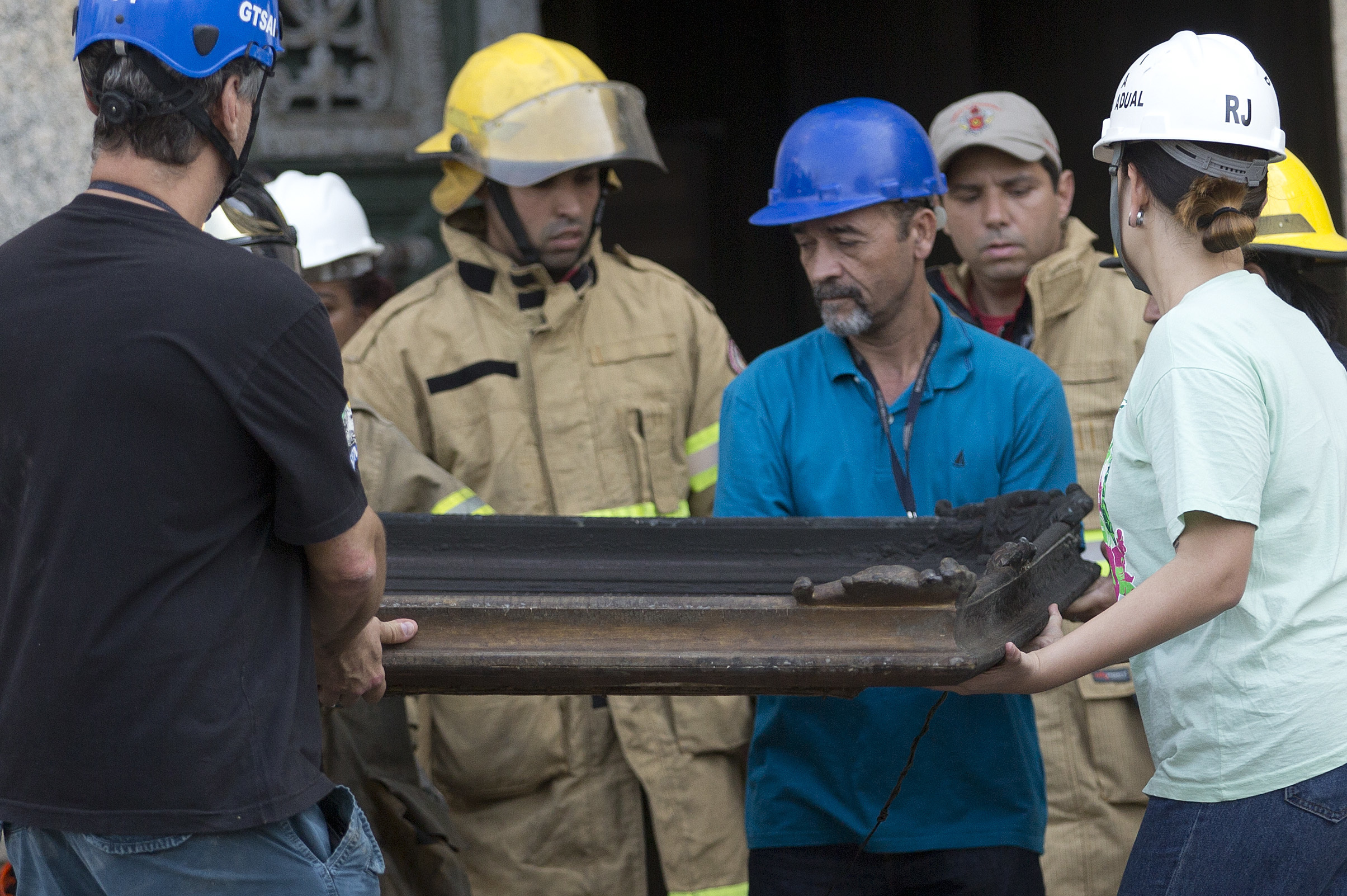 Firefighters and museum personnel carry a burnt painting from National Museum of Rio de Janeiro in Brazil on Sept. 3, 2018 following a fire.