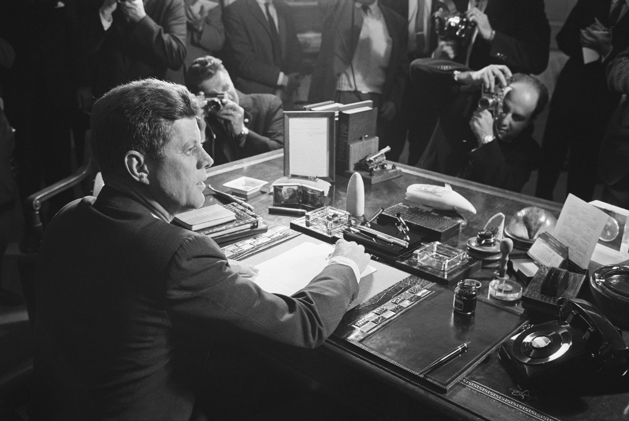 Reporters take pictures of President Kennedy behind his desk, after signing the arms embargo against Cuba on Oct. 23, 1962. The embargo effectively quarantined Cuba.