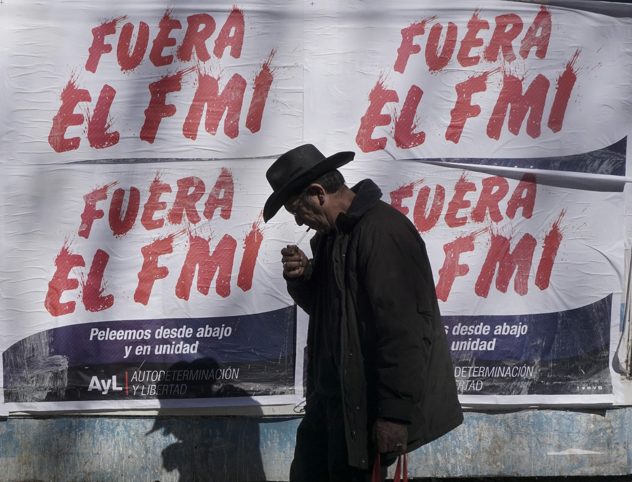 A man walks past posters rejecting the government's negotiations with the International Monetary Fund (IMF), in Buenos Aires, on September 4, 2018.