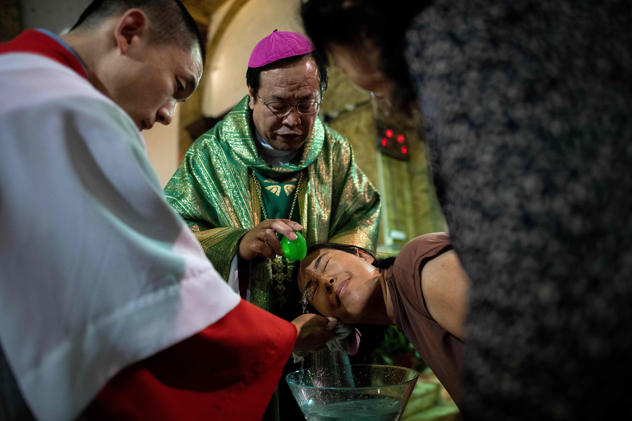 Bishop Joseph Li Shan baptizes a woman at the South Cathedral in Beijing on Sept.22