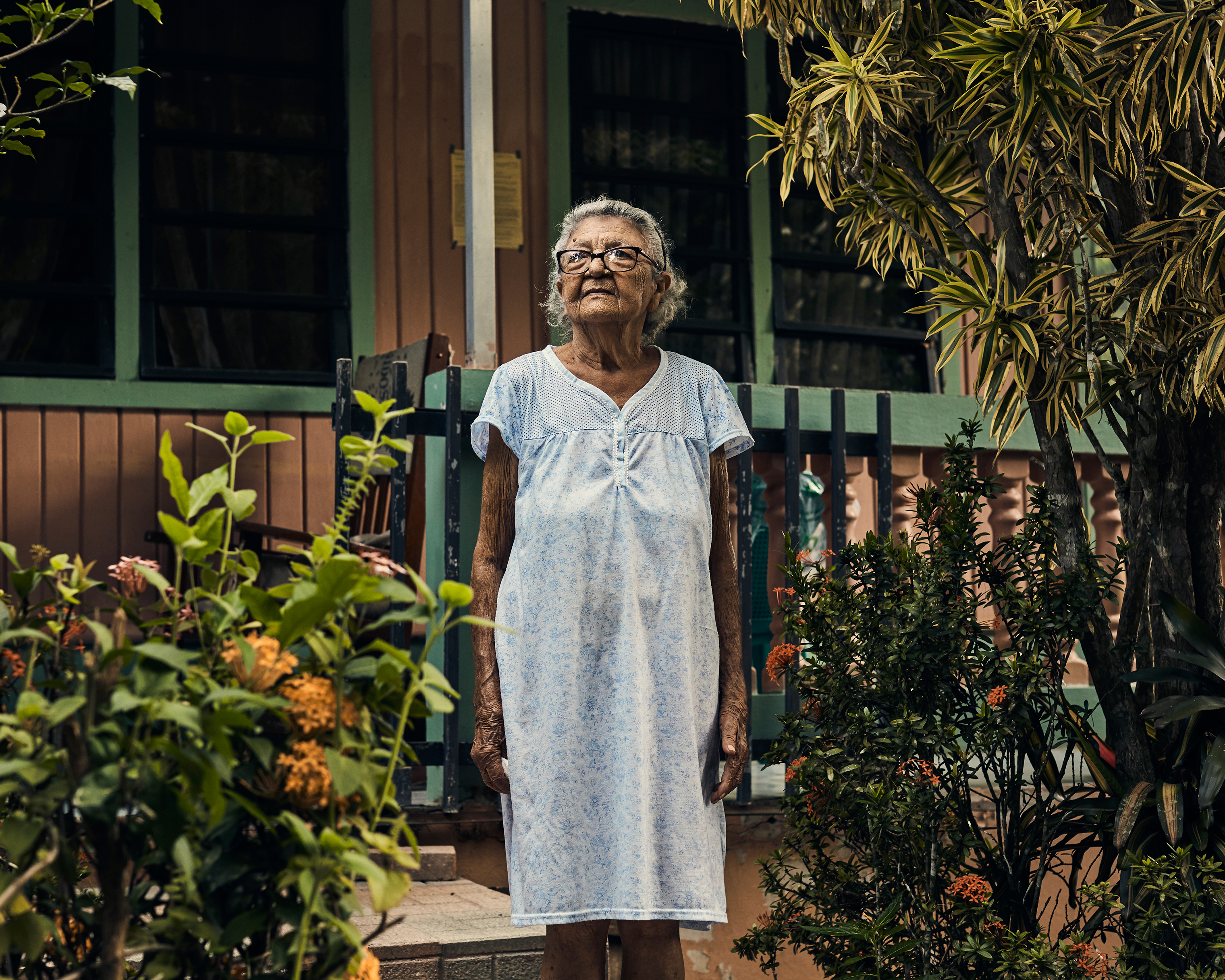 Magdalena Flores poses in front of her home in Utuado on Aug. 31. Her daughter, Maribel, died in the aftermath of the storm from asthma complications.