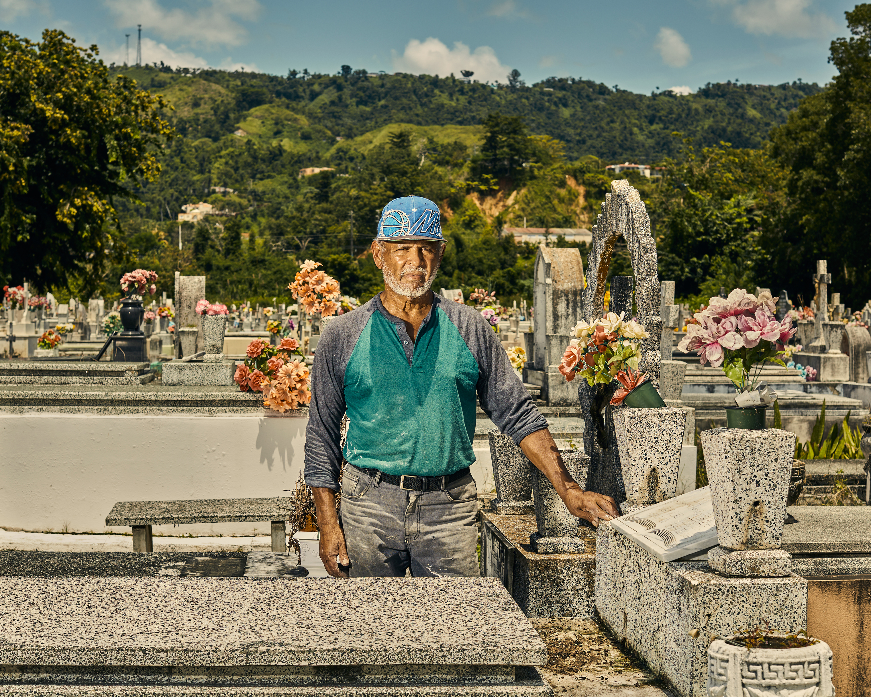 Gravekeeper Tulio Collazo Vega poses by the grave of three elderly sisters who where killed by a landslide the day Maria hit Puerto Rico.