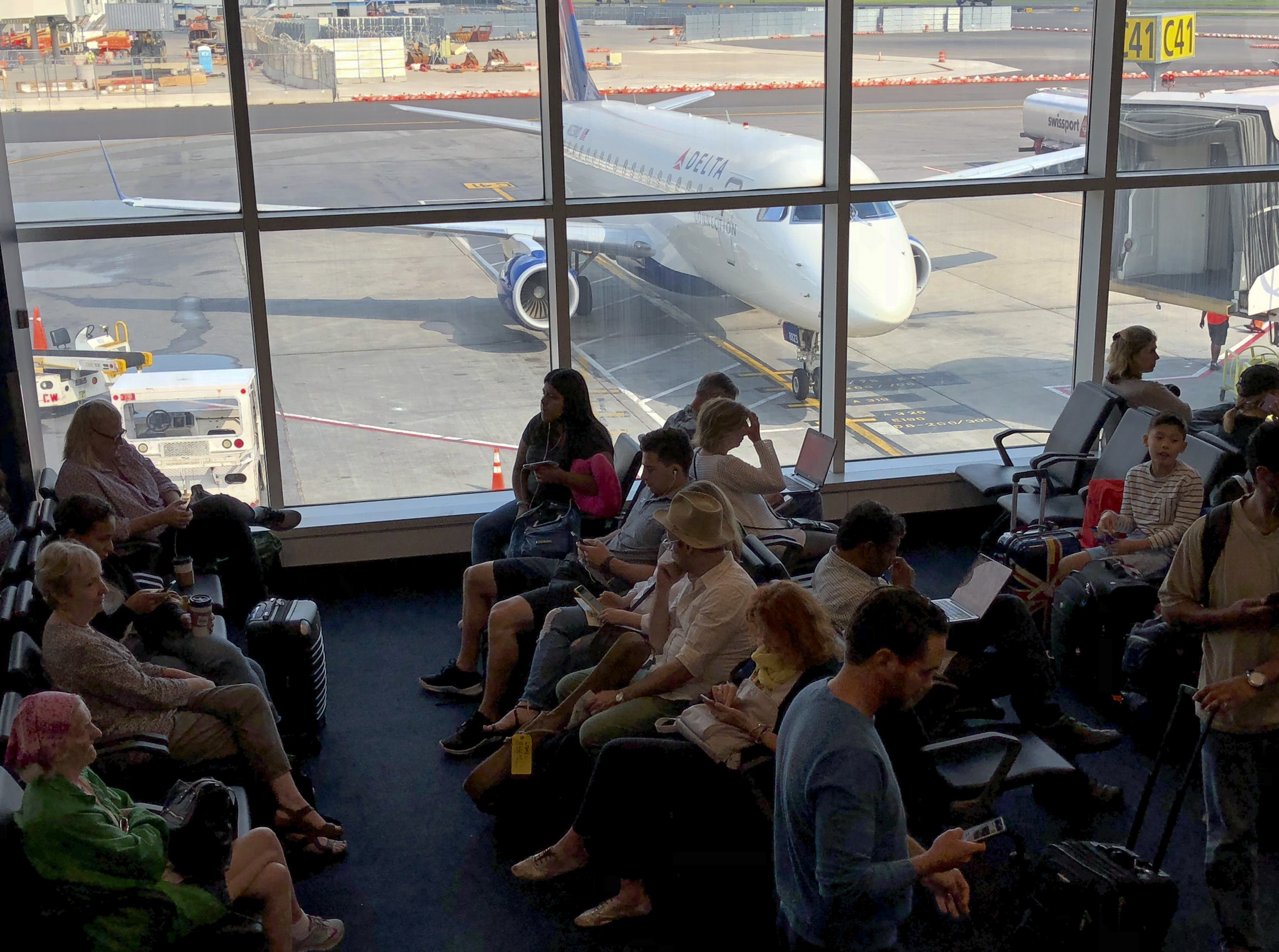 Passengers wait to board a Delta airlines plane at La Guardia  International Airport in New York on July 28, 2018.