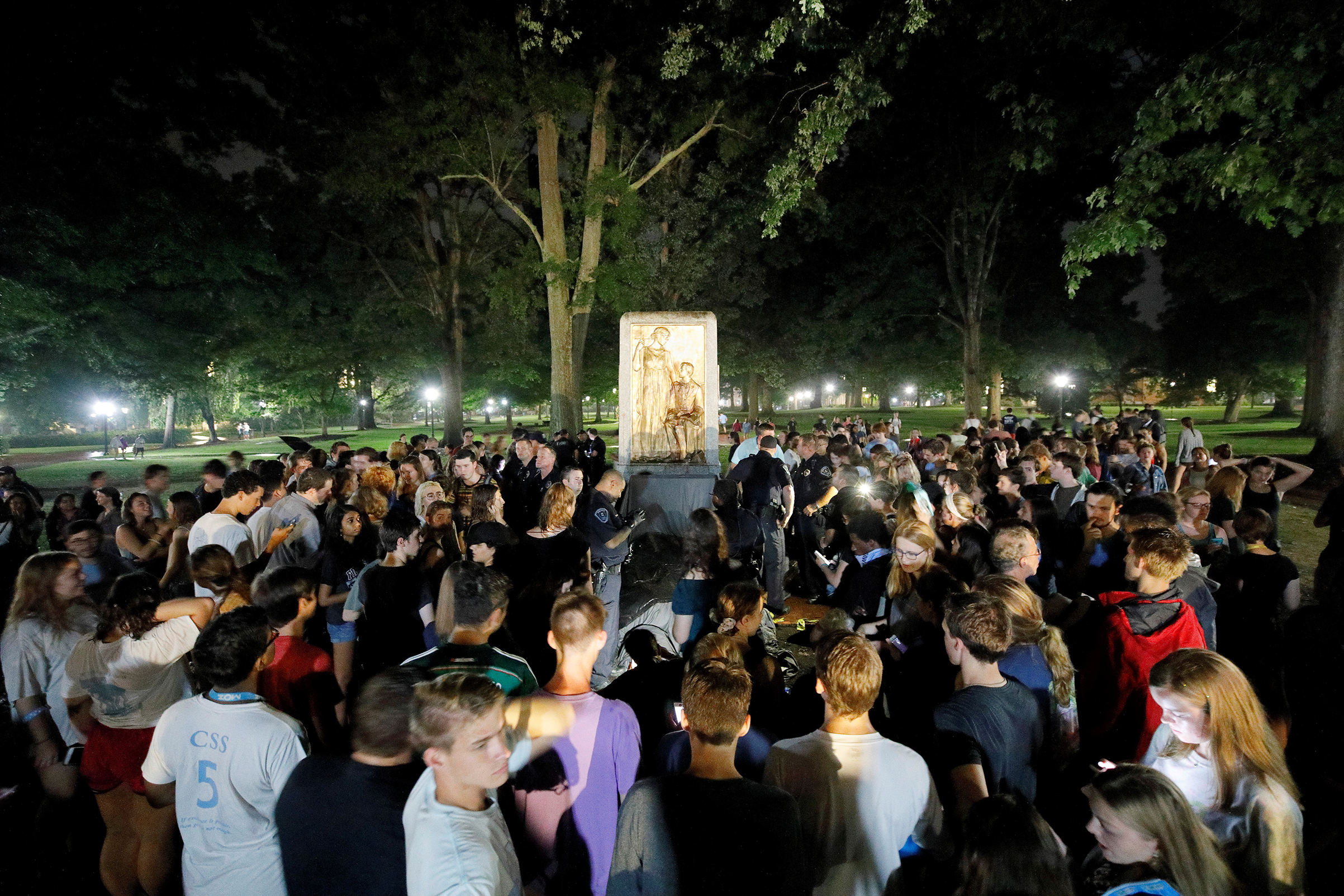 Students and protesters surround the plinth where the toppled statue of a Confederate soldier nicknamed Silent Sam once stood on the University of North Carolina campus, after a demonstration for its removal in Chapel Hill, North Carolina, on Aug. 20, 2018.