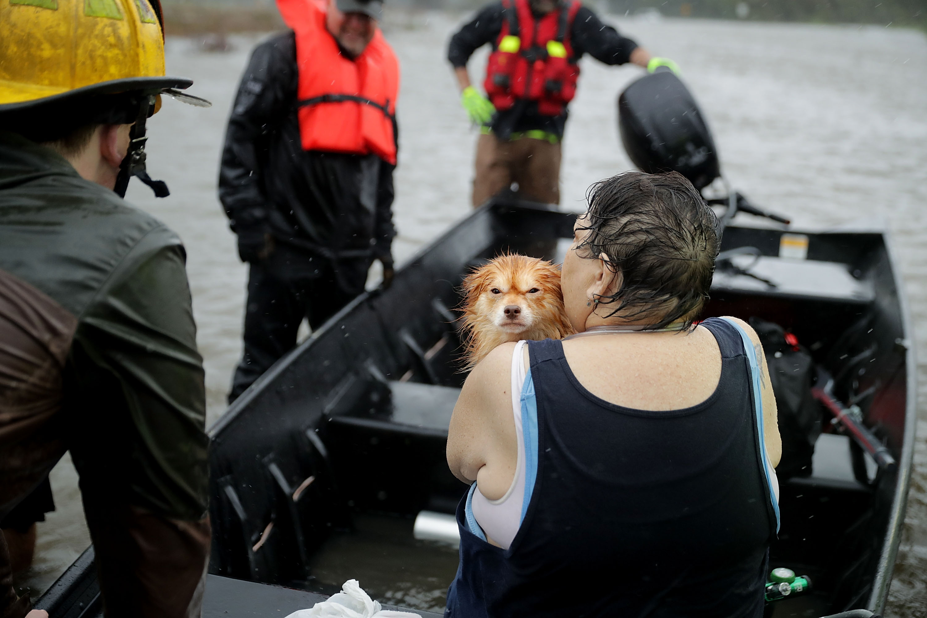 Rescue workers from Township No. 7 Fire Department and volunteers from the Civilian Crisis Response Team use a boat to rescue a woman and her dog from their flooded home during Hurricane Florence in James City, NC on Sept. 14, 2018.