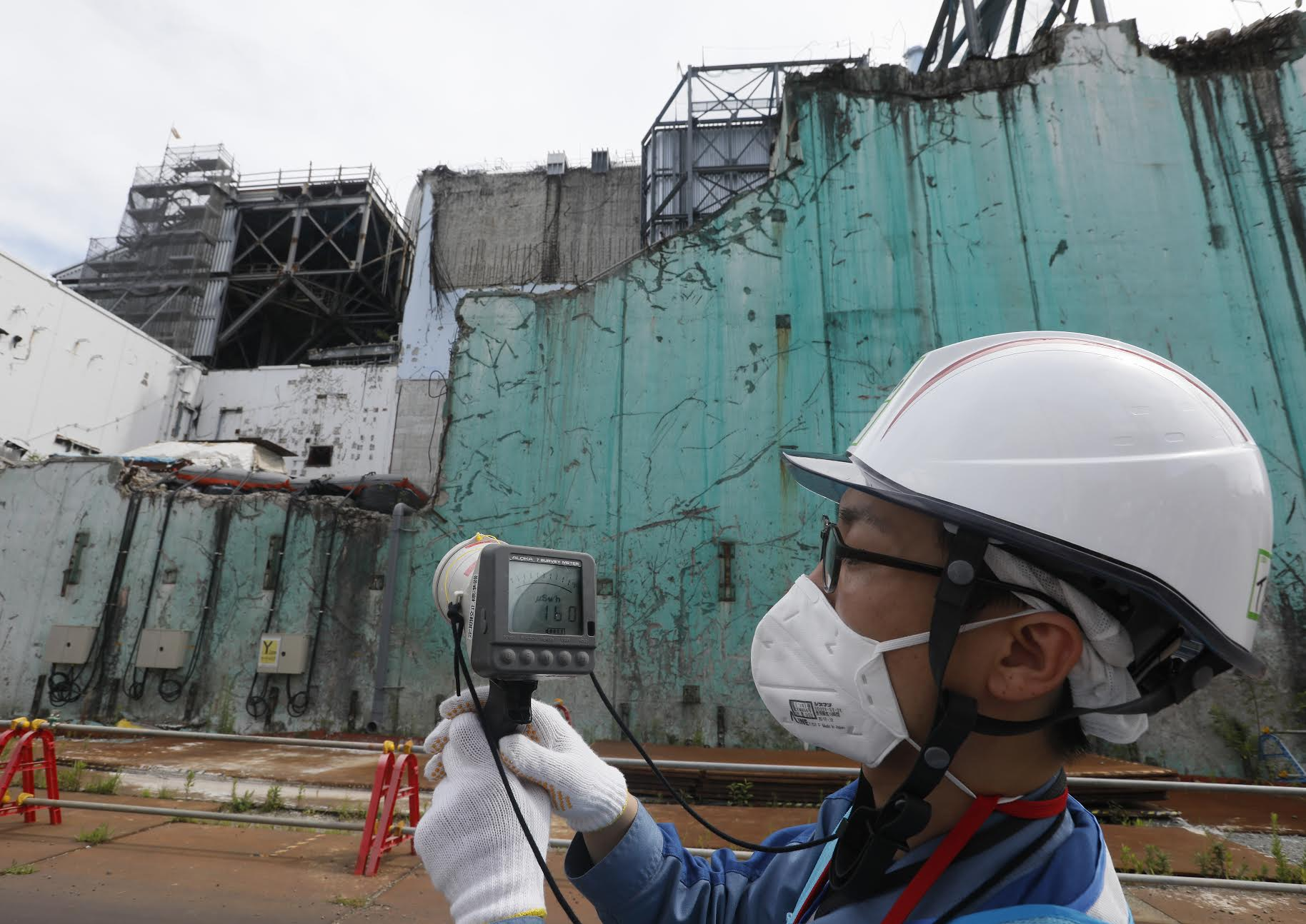 In this picture taken on July 27, 2018, a staff member of the Tokyo Electric Power Company measures radiation levels between reactor unit 2 and unit 3 (Rear) at the tsunami-crippled Tokyo Electric Power Company Fukushima Dai-ichi nuclear power plant in Okuma, Fukushima prefecture.