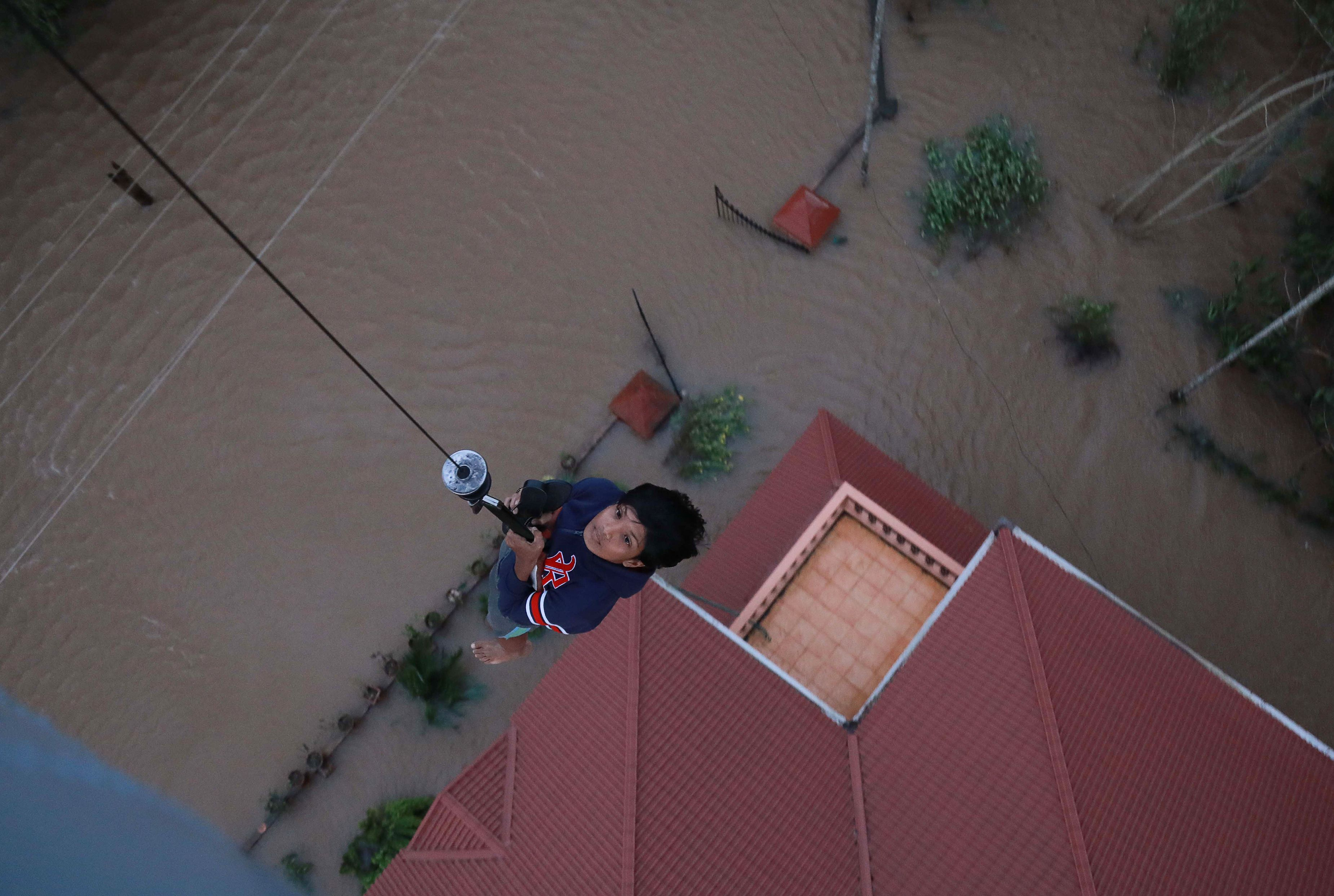 People are airlifted by Navy personnel during a rescue operation at a flooded area in Paravoor near Kochi, in the Indian state of Kerala on Aug. 18, 2018.