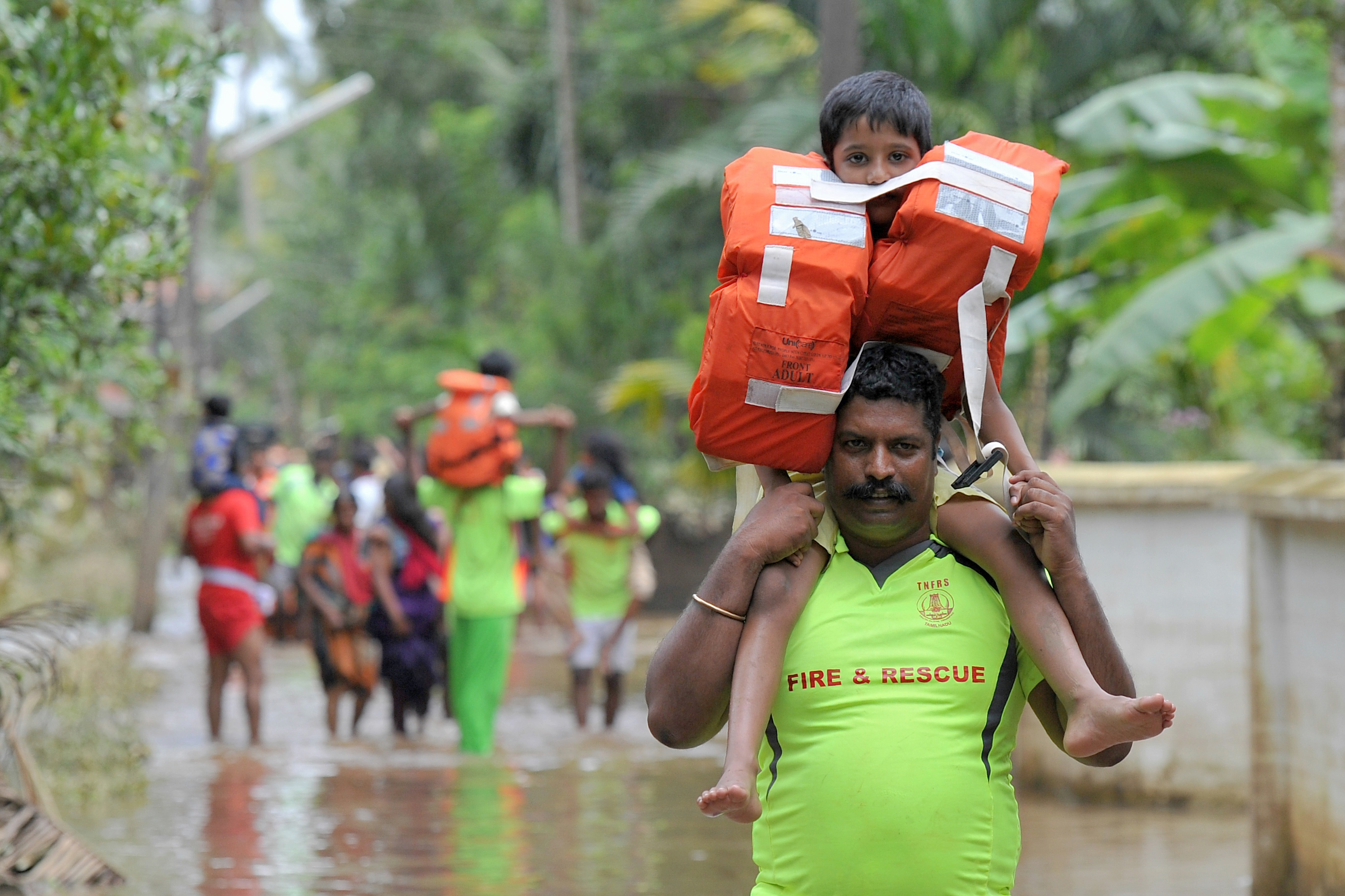Kerala and Tamil Nadu Fire Force personnel carry children on their shoulders through flood waters during a rescue operation in Annamanada village in Thrissur District, in the south Indian state of Kerala, on Aug. 19, 2018.