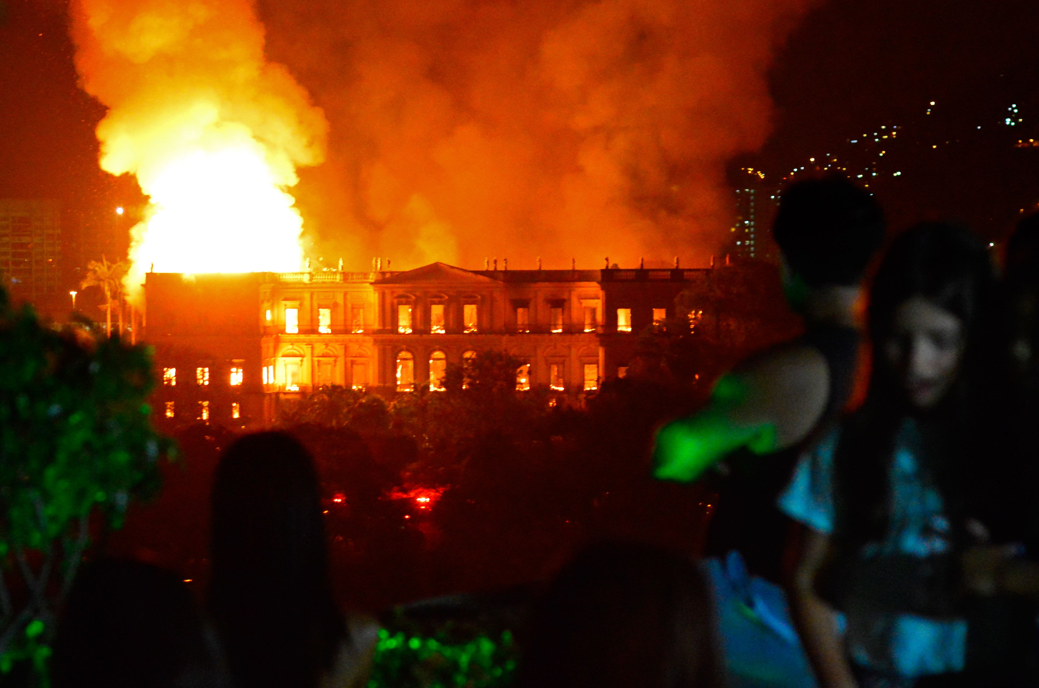 People watch as a massive fire engulfs the National Museum in Rio de Janeiro in Brazil on Sept. 2, 2018.