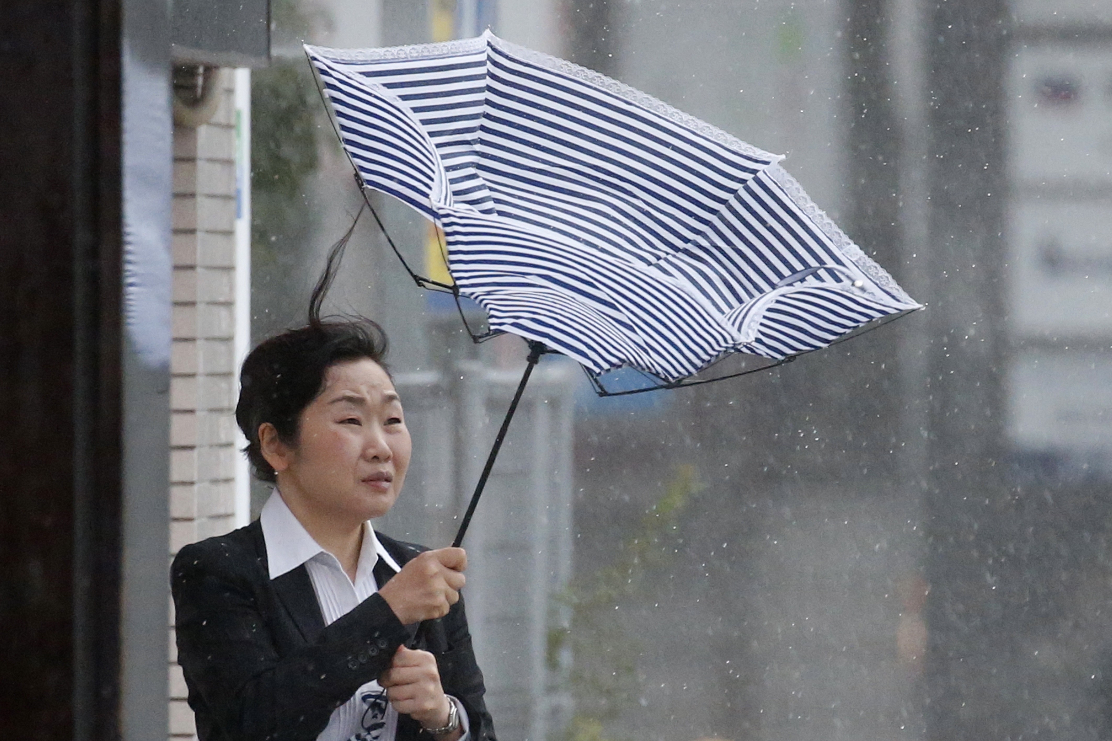 A woman using an umbrella struggles against strong wind and rain caused by Typhoon Jebi, in Tokyo, Japan, Sept. 4, 2018.