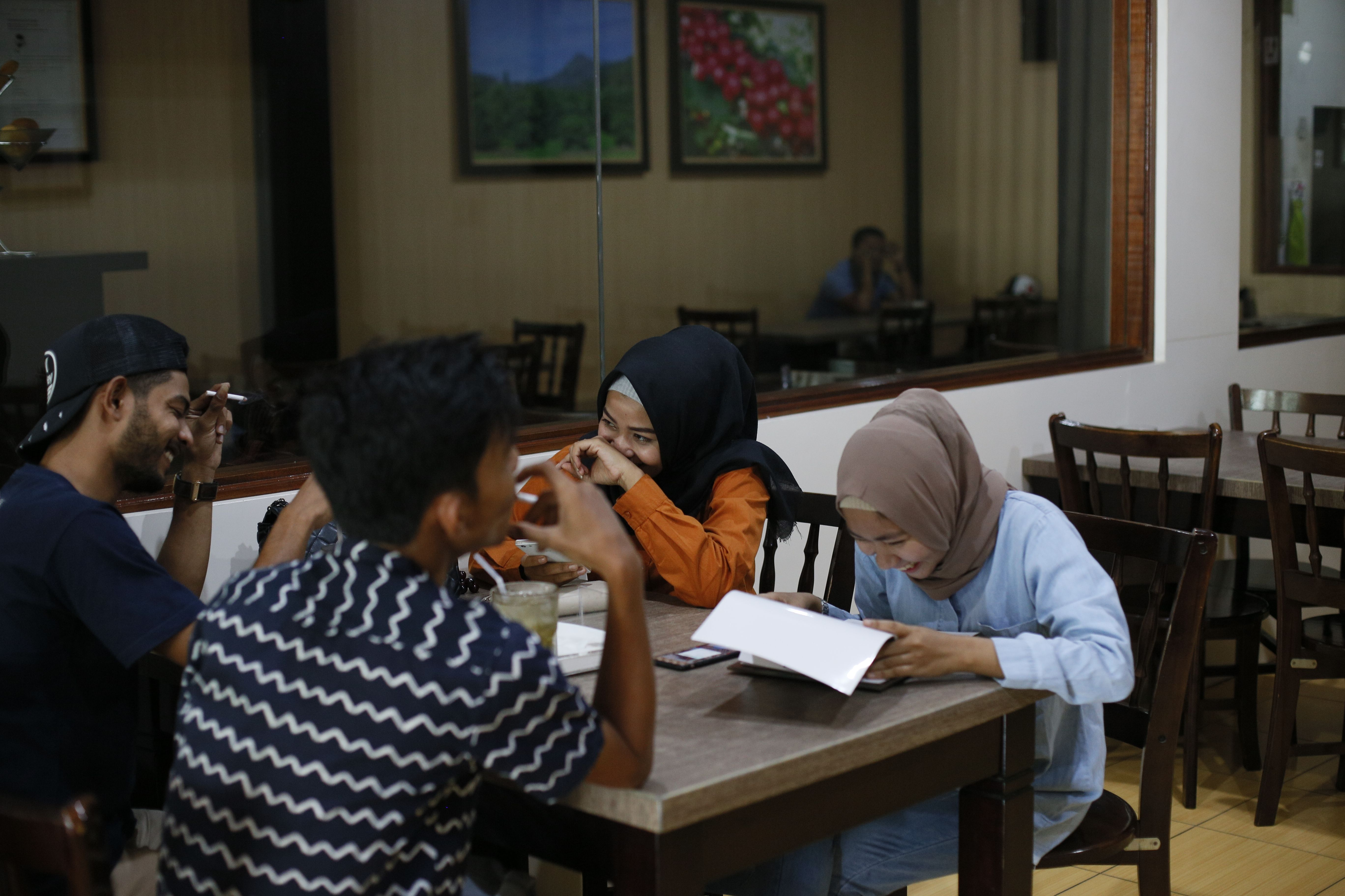 Men and women sit at a restaurant in Bireun district in Indonesia's Aceh province, on Sept. 5, 2018.