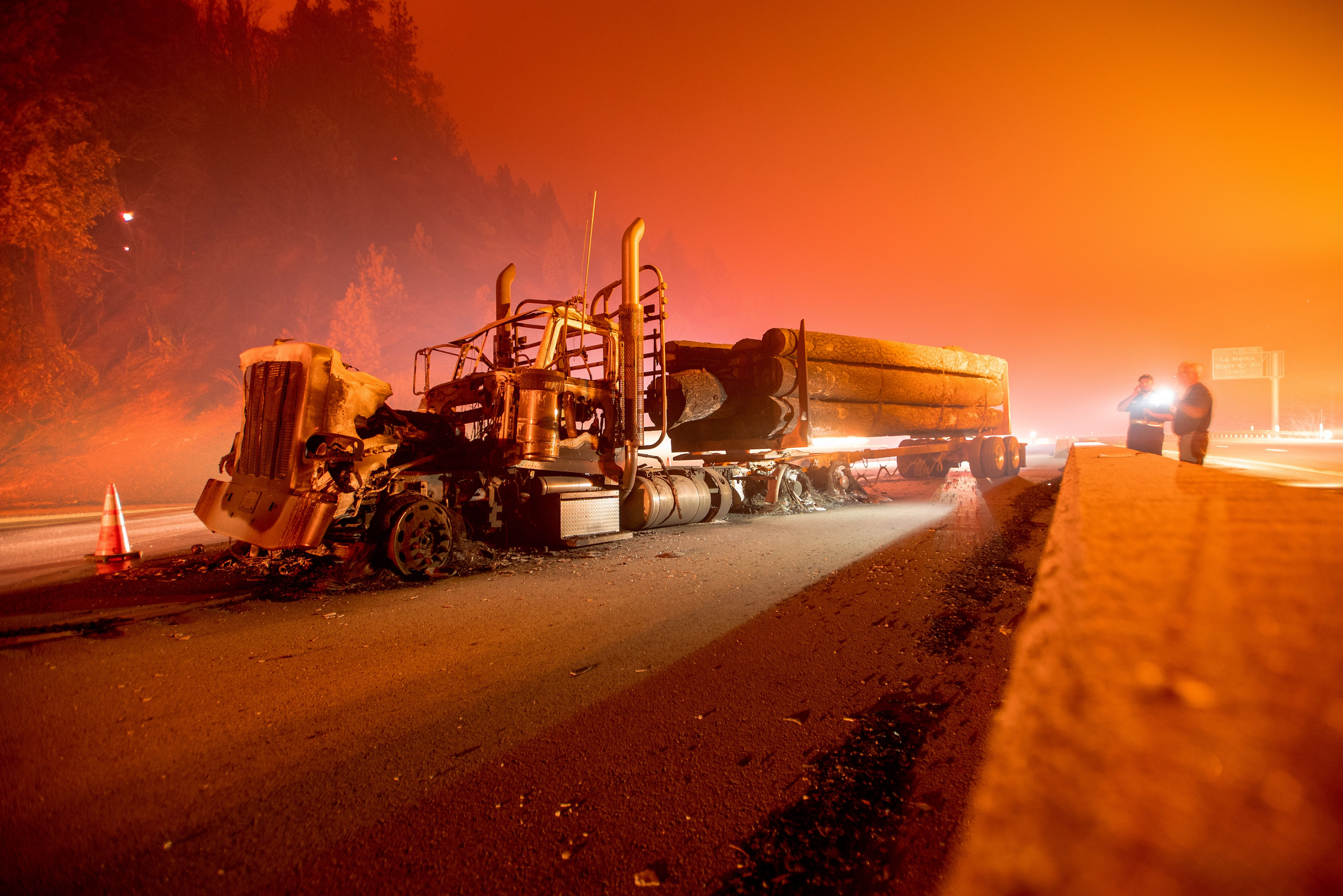 An abandoned smoldering truck rests along interstate 5 after the Delta Fire tore through the region and jumped the road in Delta, south of Pollard Flat, California on Sept. 5, 2018.