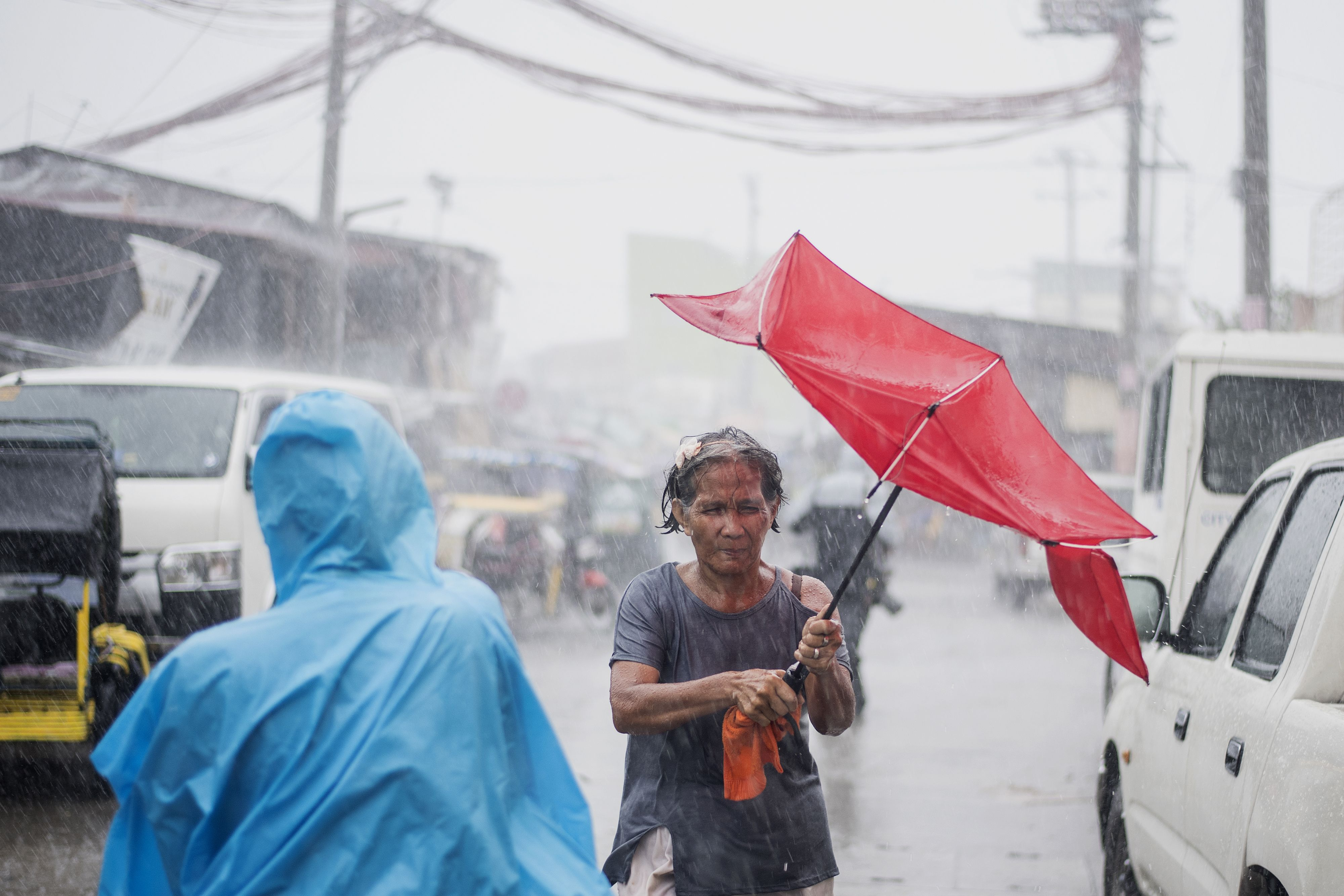 A woman holds her umbrella during heavy rains caused by Typhoon Mangkhut in Manila on Sept. 15, 2018.