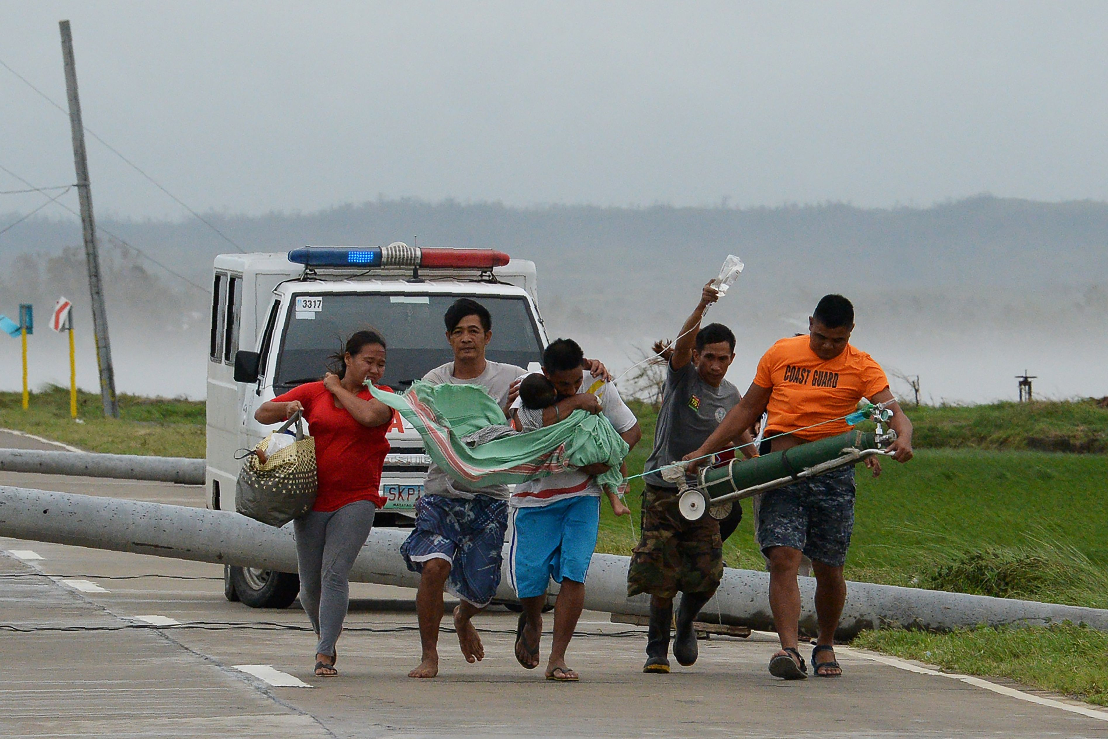 A father carries his sick child as it is being transferred to another car after their ambulance is stuck on a highway by toppled electric posts caused by strong winds after Typhoon Mangkhut hit Baggao town in Cagayan province, north of Manila on Sept. 15, 2018.