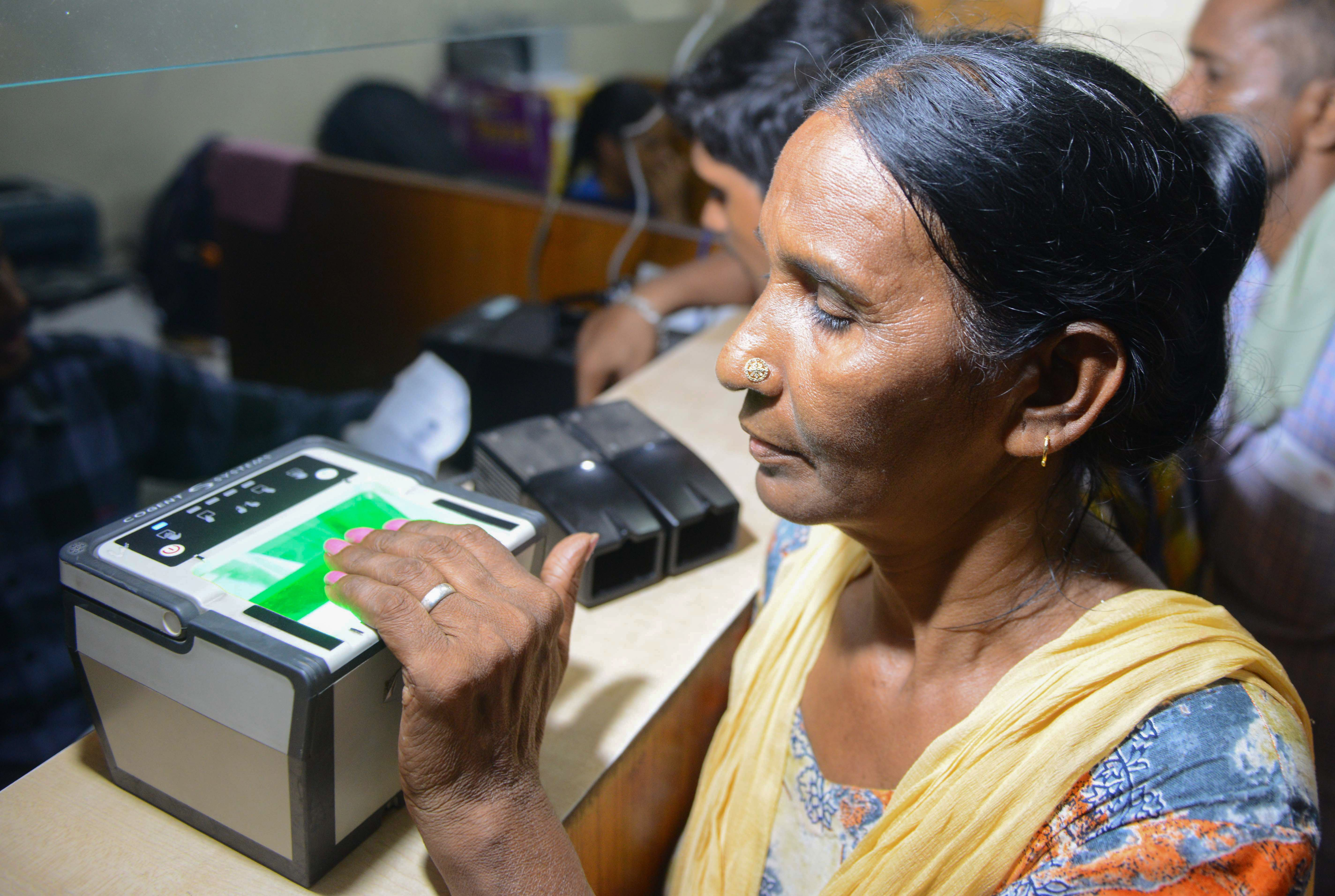 An Indian woman has her fingerprints read during the registration process for Aadhaar cards on July 17, 2018.