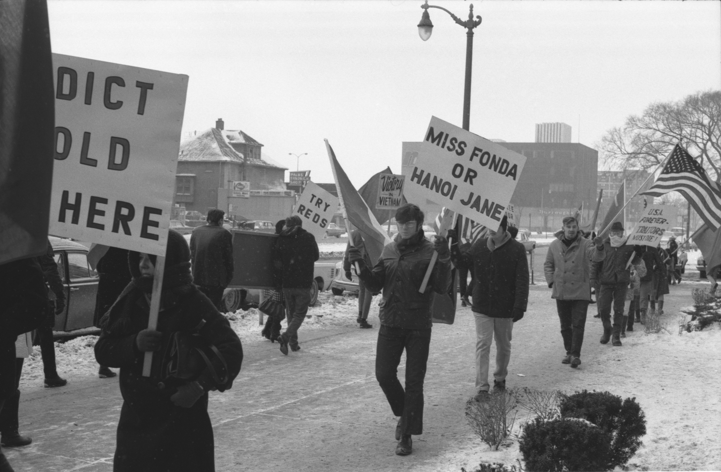 Protesters carrying signs protesting Jane Fonda's visit to Hanoi outside Howard Johnson's Hotel in Detroit during the time of the  Winter Soldier Investigation,  Detroit, 1971.