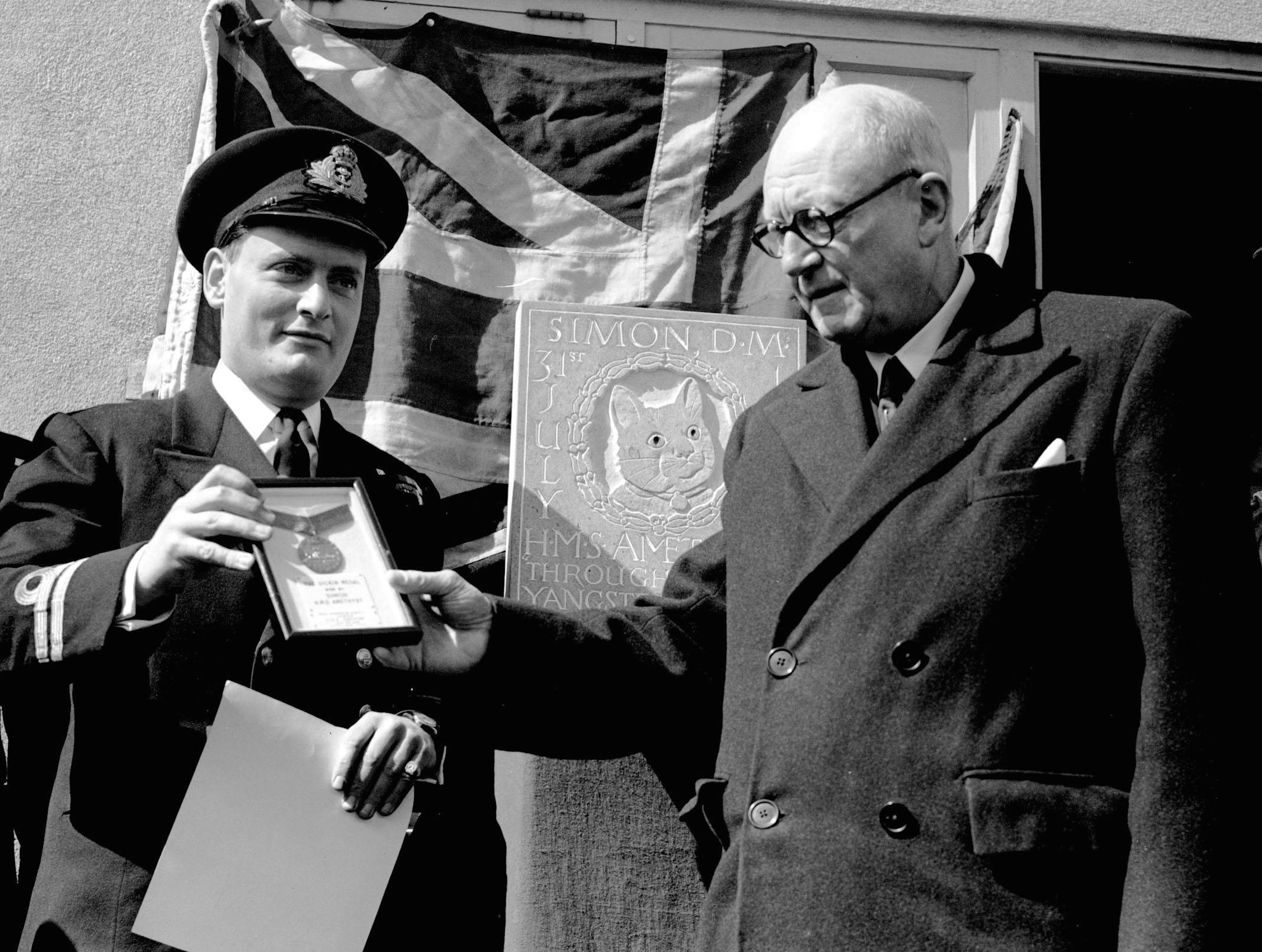 Alderman W. Harry Taylor with Lieutenant Geoffrey Weston (L) who assumed command of the frigate Amethyst, unveiling a plaque in memory of the ship's cat Simon, in Plymouth, after the cat received the Dickin Medal, for catching rats and protecting food supplies during the time the ship was trapped by the Chinese