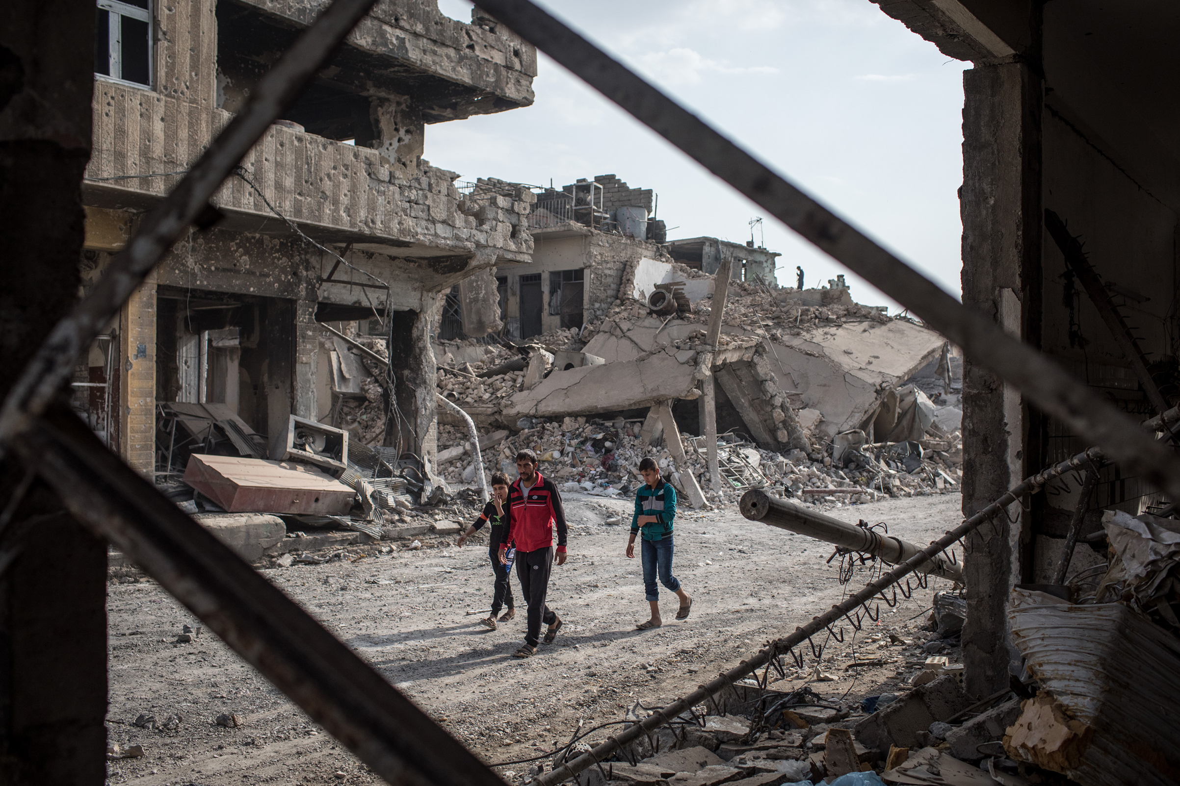 People walk amongst rubble from destroyed buildings in an outer neighborhood of the Old City in West Mosul on November 6, 2017 in Mosul, Iraq.