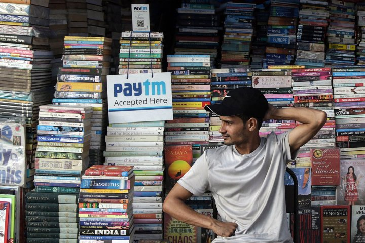 An Indian book seller sits next to a sign indicating Paytm Mobile Phone Payment Technology is accepted to receive payment from customers due to lack of Indian currency notes in a market in Mumbai India, Nov. 28 November.