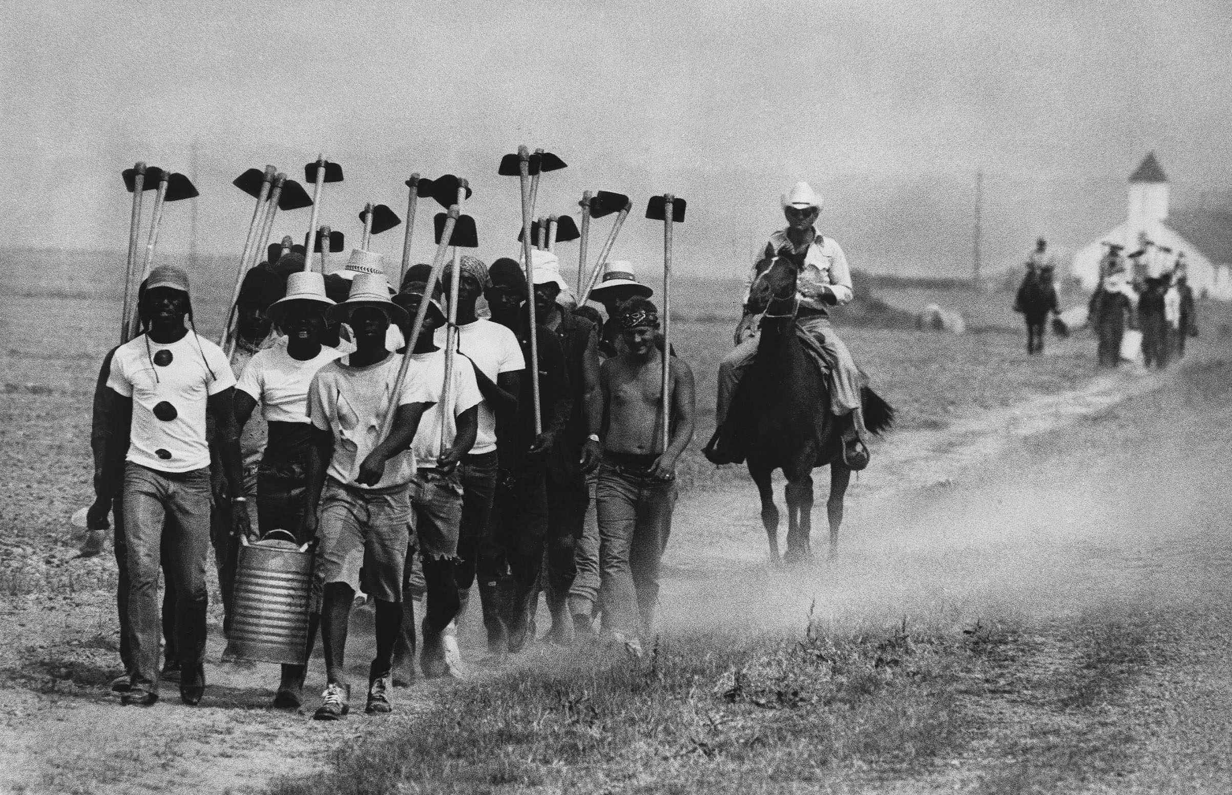Inmates at Louisiana State Prison in Angola, La., march down a dusty trail on May 30, 1977, en route to working in the fields.