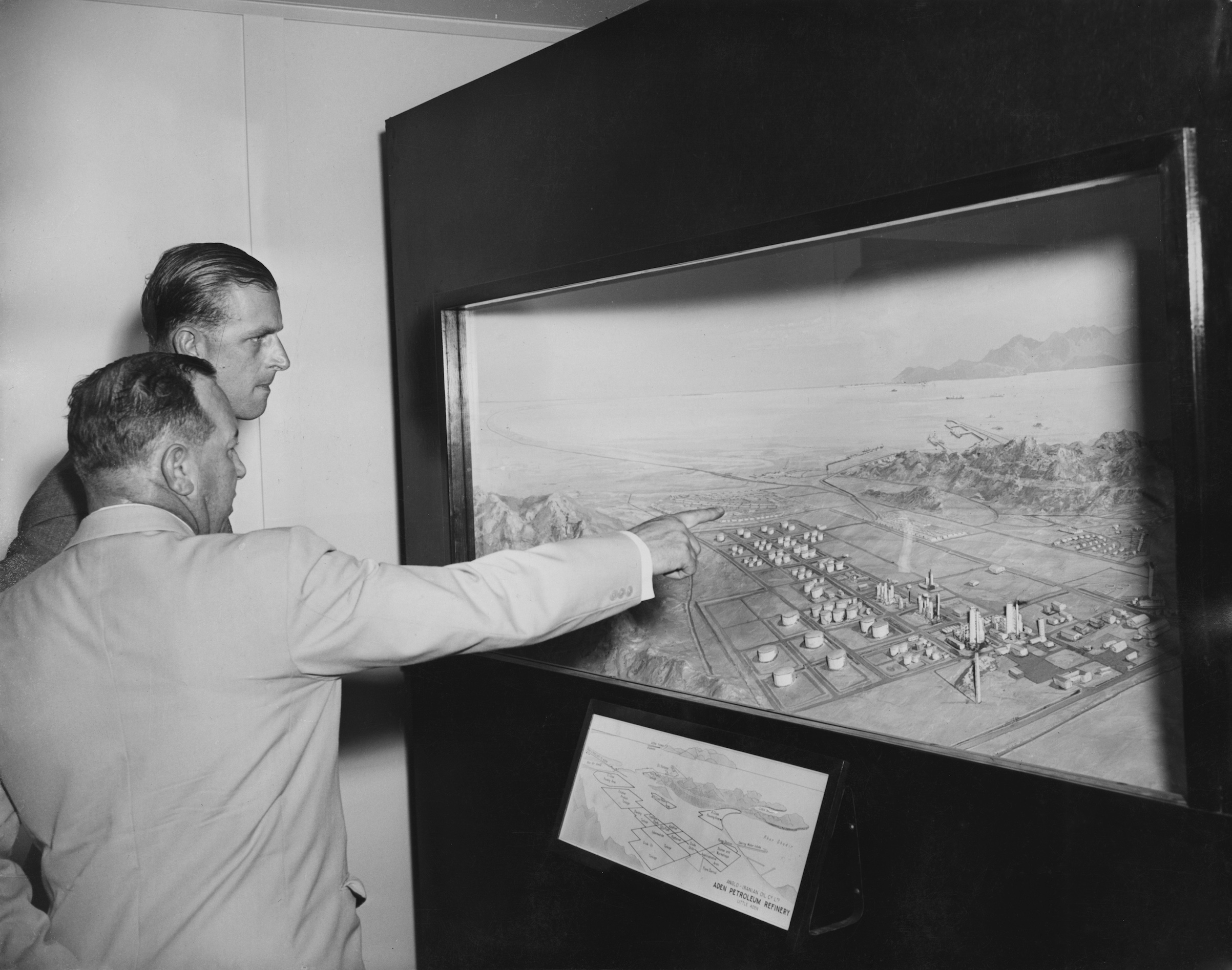 Prince Philip, Duke of Edinburgh visits the Aden Petroleum Refinery, an Anglo-Iranian Oil Company refinery at Little Aden during a Commonwealth visit to Yemen, April 27,1954. Here he is shown a panoramic model of the refinery by General Manager A. W. G. Trantor.