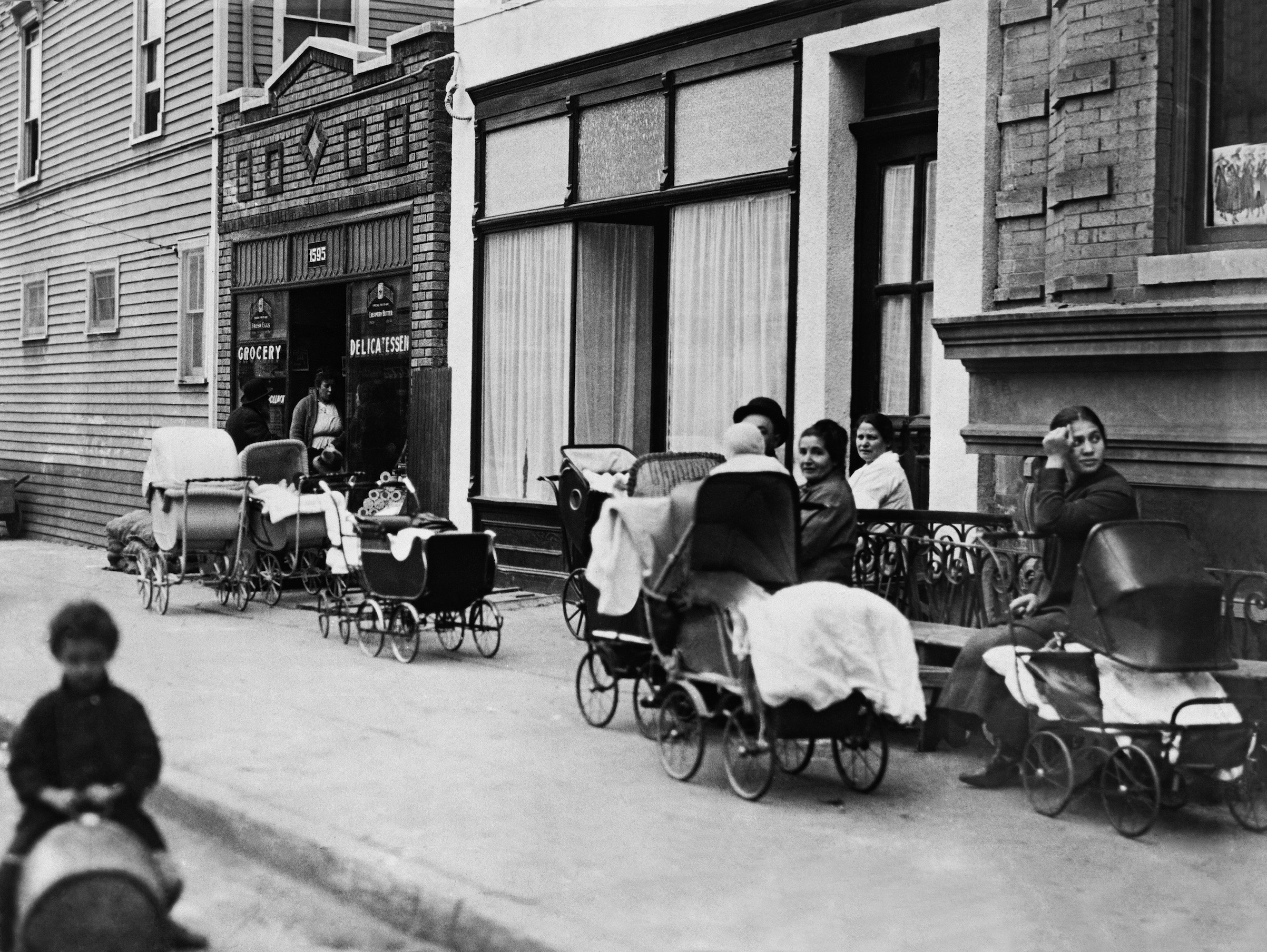 Women and men sitting with baby carriages in front of the Sanger Clinic on Amber Street in Brooklyn, N.Y., in October of 1916.