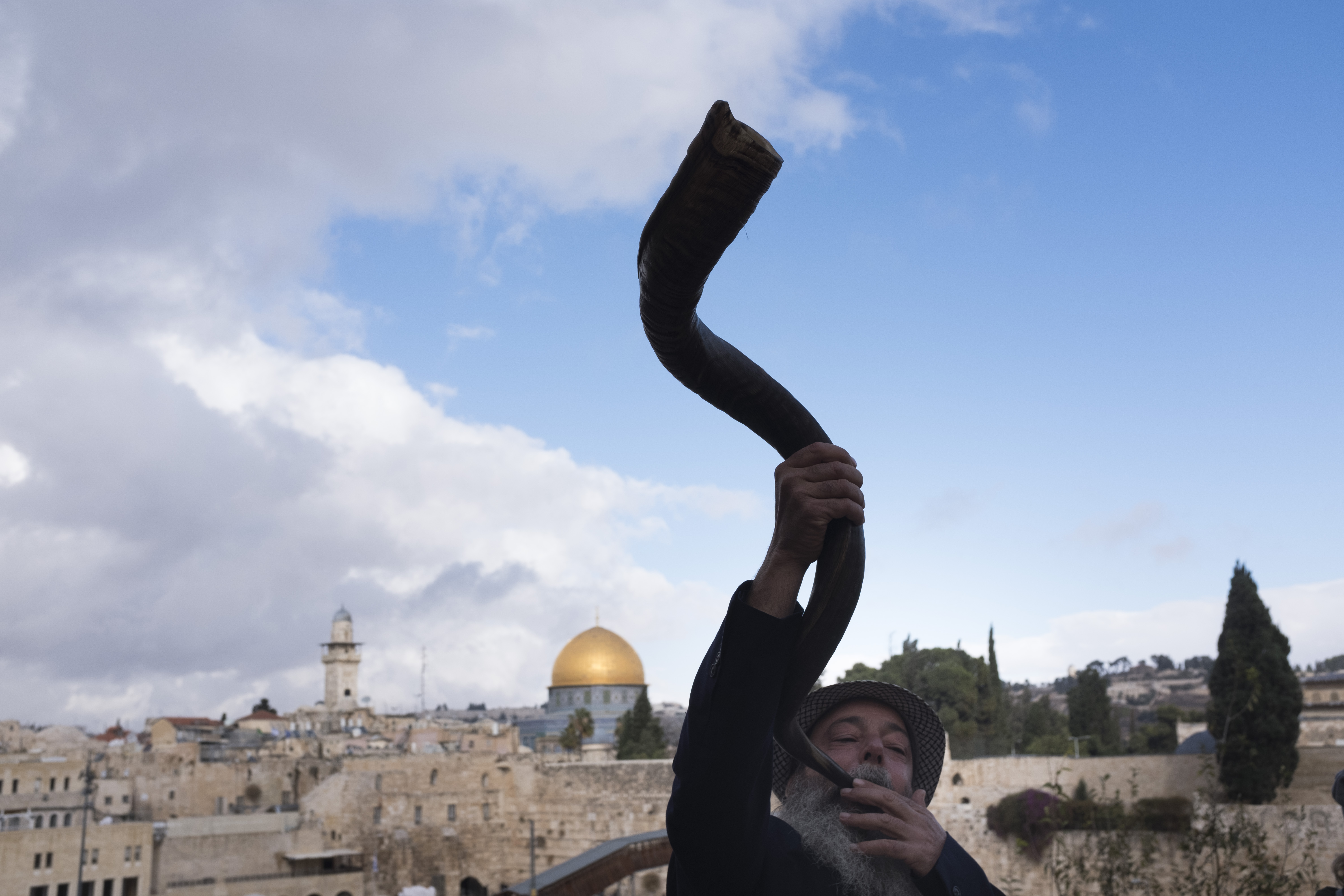 A man blows the shofar (ram's horn.)