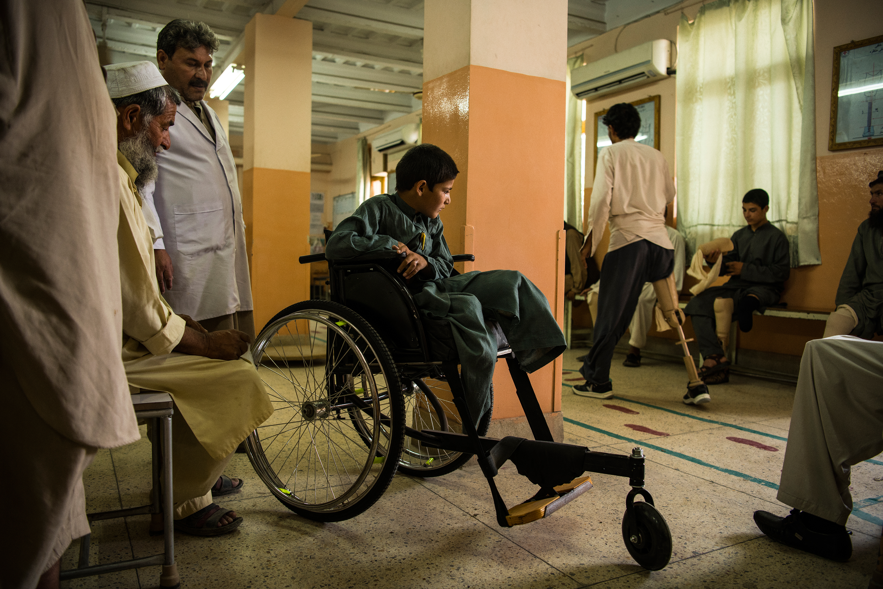 Abdul Rashid watches a patient practice with a prosthetic leg at the orthopedic center on June 27.