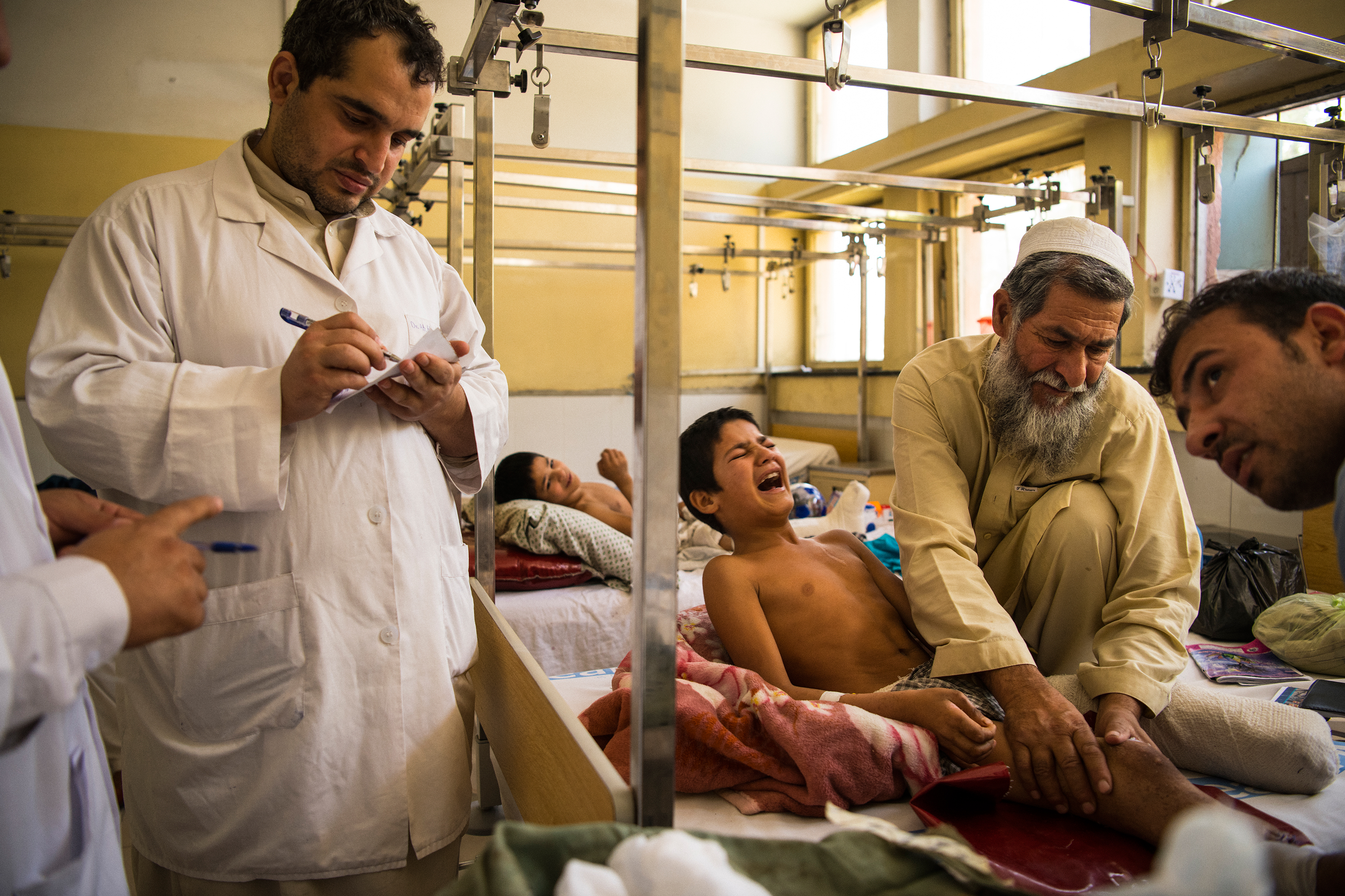 Abdul Rashid's wounds are cleaned, drained and redressed prior to he and his brothers' discharge from Nangarhar Regional Hospital after a month-long stay.