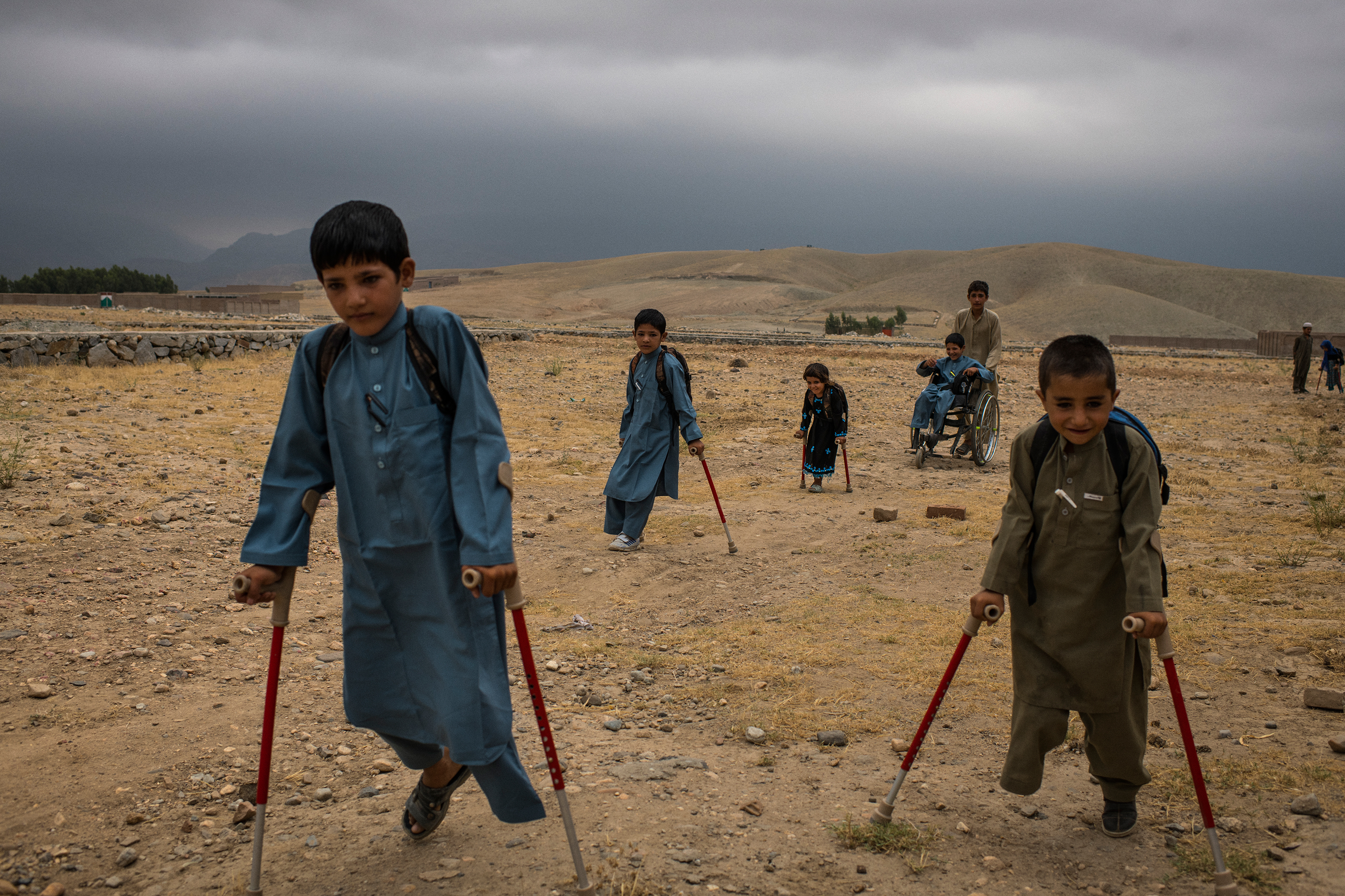 From left, Bashir, Mangal, Marwa, Abdul Rashid (in wheelchair), Aman and, in the distance, Rabia are helped by their cousins on July 23 to a nearby house where they attended school while recovering.