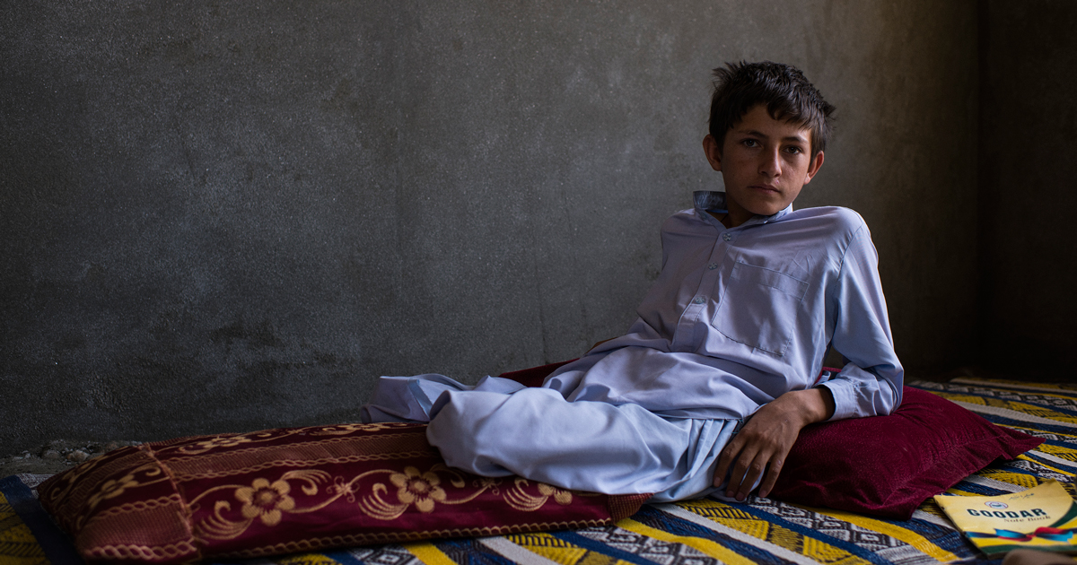 """Shafiqullah, the eldest of the injured children, at home on June 25, a month after leaving the hospital. His schoolbooks have rarely been out of reach during his recovery. """"Since the accident,"""" one cousin said, he is """"even more driven to study."""""""