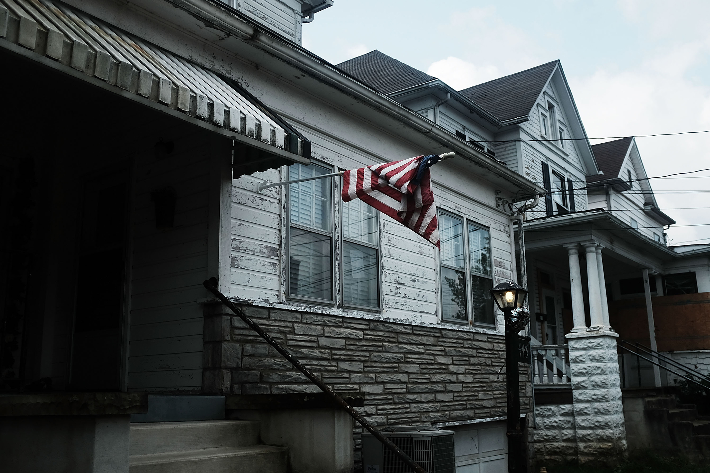An American flag hangs outside of a home in Clarksburg, WV on Aug. 22, 2018, a state still struggling with endemic poverty and opioid abuse.
