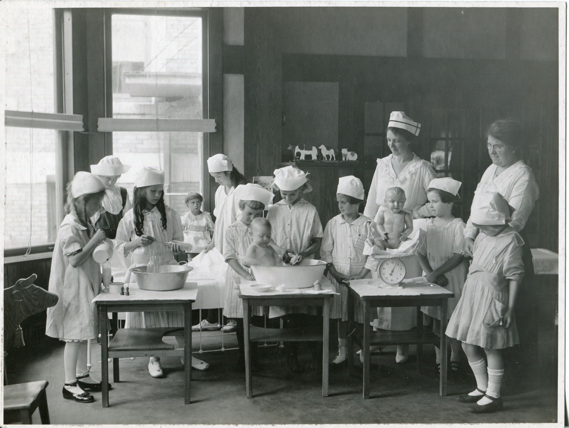 The Little Mothers League of New York State, circa 1940. Founded in 1908, the Little Mothers Leagues were part of a larger focus in public health aimed at reducing an infant mortality rate that hovered at 30% in poor urban communities. Many of those deaths could be linked young children in these families who were charged with the care of their infant siblings while their mothers' worked.