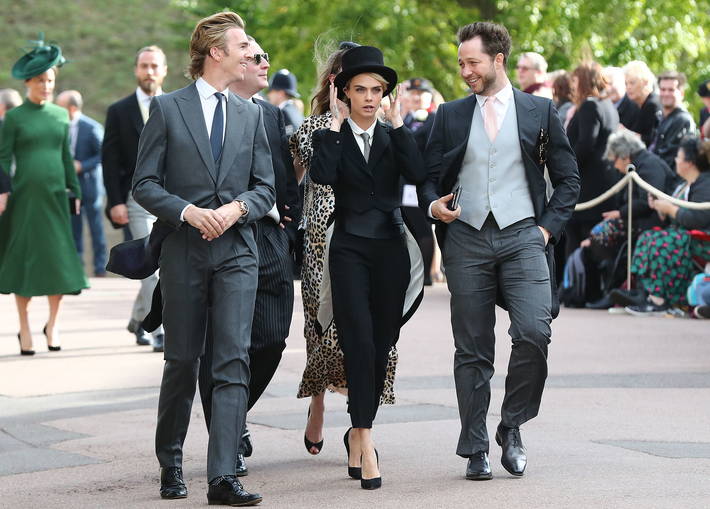 Cara Delevingne (C) arrives with her brother-in-law James Cook (L) and US journalist Derek Blasberg (R) to attend the wedding of Britain's Princess Eugenie of York to Jack Brooksbank at St George's Chapel, Windsor Castle, in Windsor, on October 12, 2018. (Photo by Gareth Fuller / POOL / AFP)        (Photo credit should read GARETH FULLER/AFP/Getty Images)