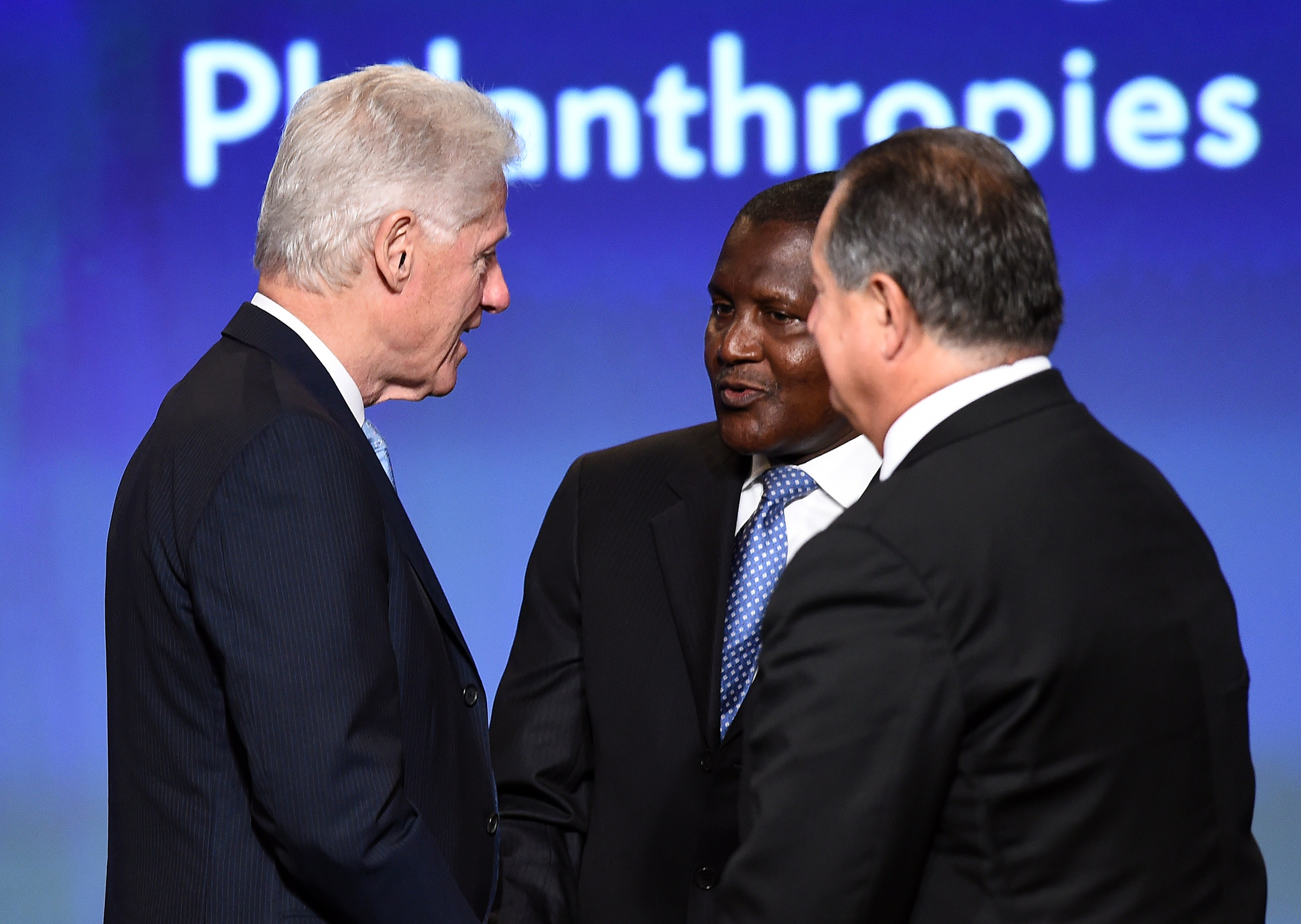 Former U.S. President Bill Clinton (L) speaks with Aliko Dangote (C), President and CEO, Dangote Group, and Andrew N. Liveris, President, Chairman & CEO, at the end of a panel discussion during US-Africa Business Forum on the sideline of the US-Africa Leaders Summit in Washington, DC, on August 5, 2014.