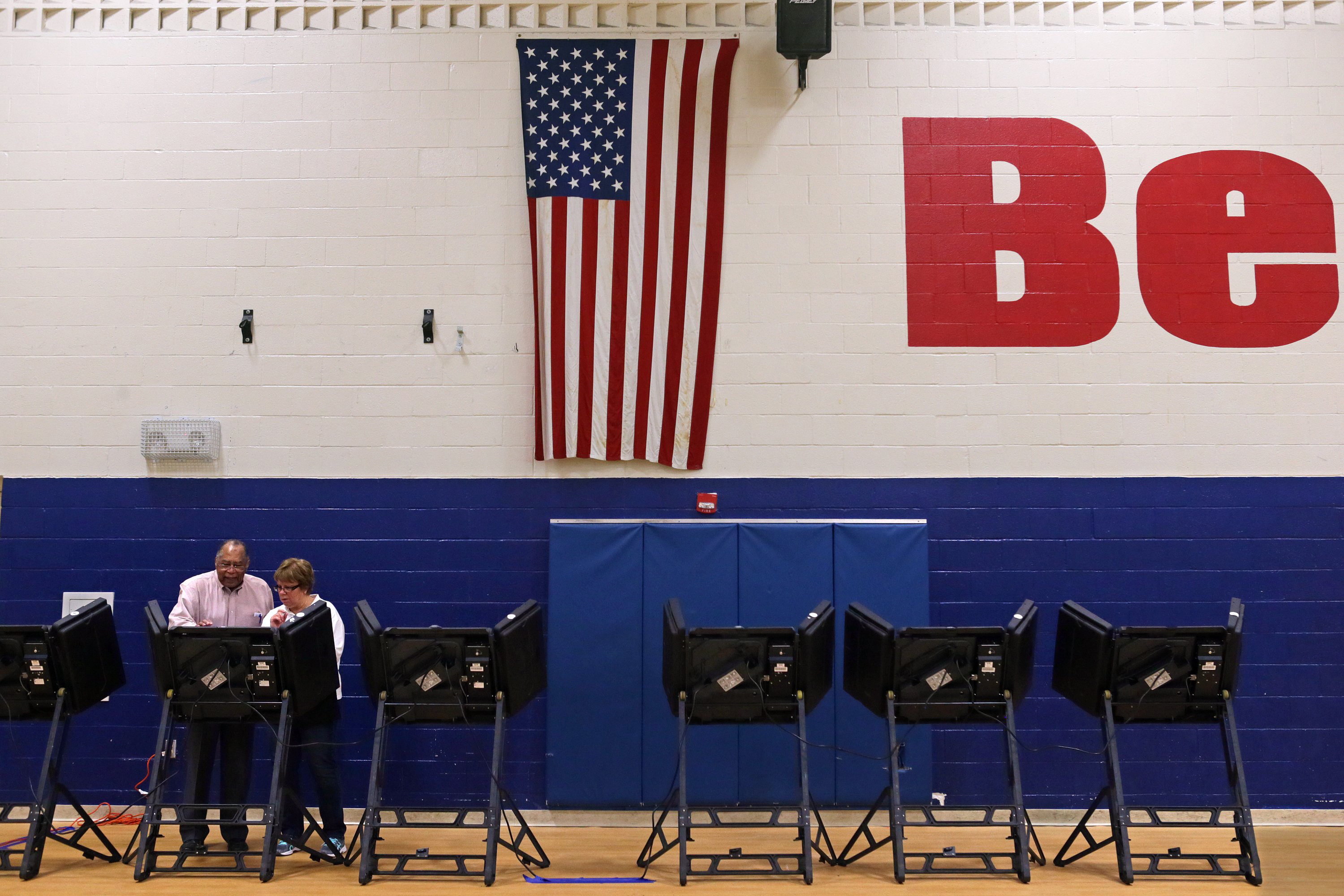An assistant supervisor of voting at Bernard School in Mehlville, right, demonstrates how to use the electronic voting machine for voting in the Republican and Democratic primaries on Tuesday, March 15, 2016, at Bernard School in Mehlville, Mo.