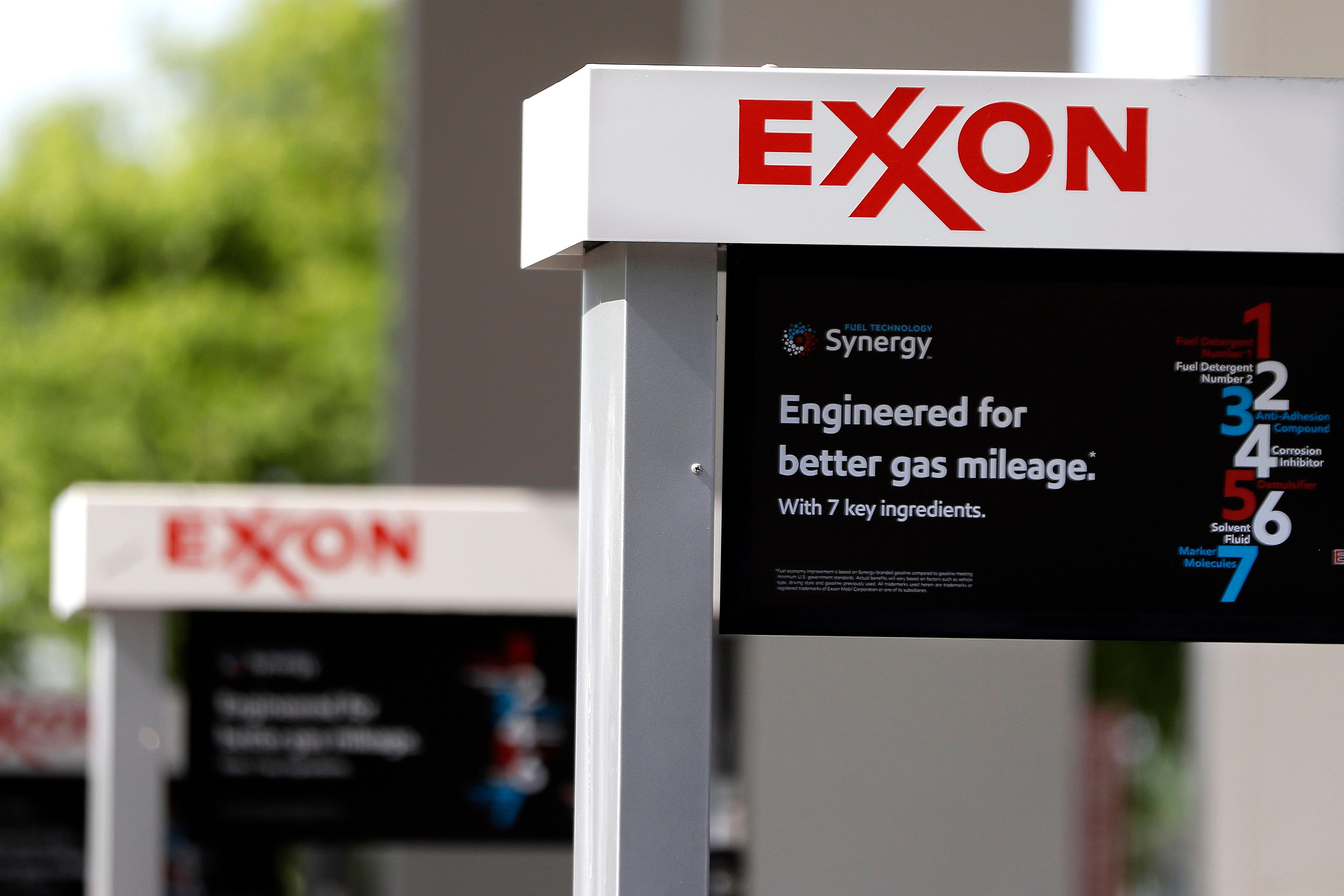 This April 25, 2017, photo, shows Exxon service station signs in Nashville, Tenn. The gasoline company is being sued by the state of New York for misleading investors regarding climate change.